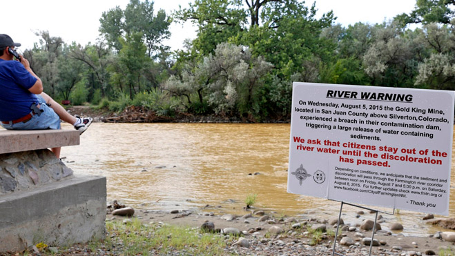 Aug. 8, 2015: A warning sign from the city is displayed in front of the Animas River as orange sludge from a mine spill upstream flows past Berg Park in Farmington, N.M.