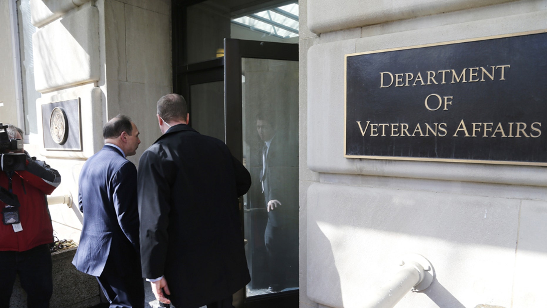 U.S. Department of Veterans Affairs Secretary Robert McDonald (L) departs into the building after delivering an apology, for recent misstatements about his military record, to reporters outside VA headquarters in Washington, February 24, 2015.  REUTERS/Jonathan Ernst    (UNITED STATES - Tags: POLITICS MILITARY) - GM1EB2P0CWL01