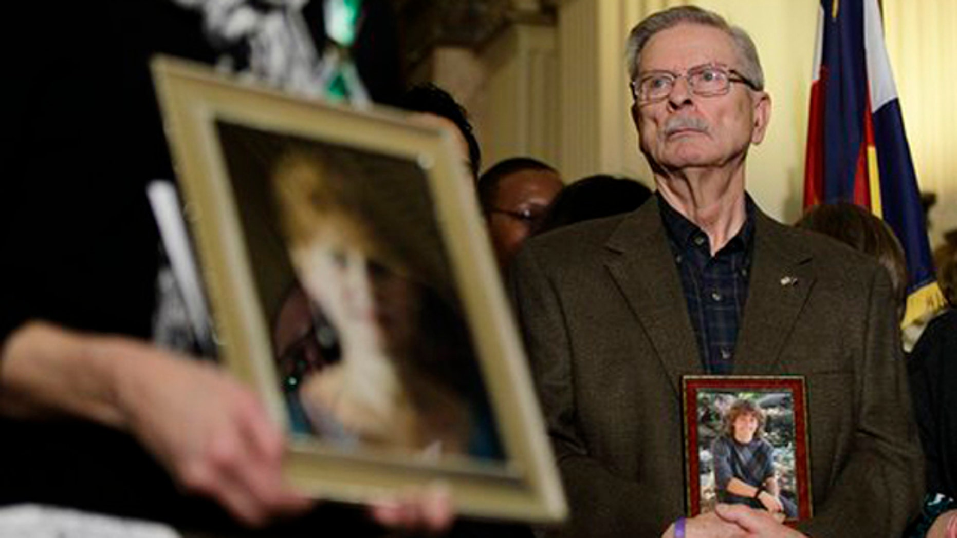 Bill Hoover carries a photo of his grandson AJ Boik, who was killed in the July, 2012 Aurora movie theatre massacre, during a news conference at which Colorado State legislators unveiled  gun control measures, at the State Capitol, in Denver, Tuesday Feb. 5, 2013. Among the proposed measures is a new bill that would hold manufacturers, sellers, and owners of assault weapons liable and responsible for damages caused by shootings with those weapons. (AP Photo/Brennan Linsley)