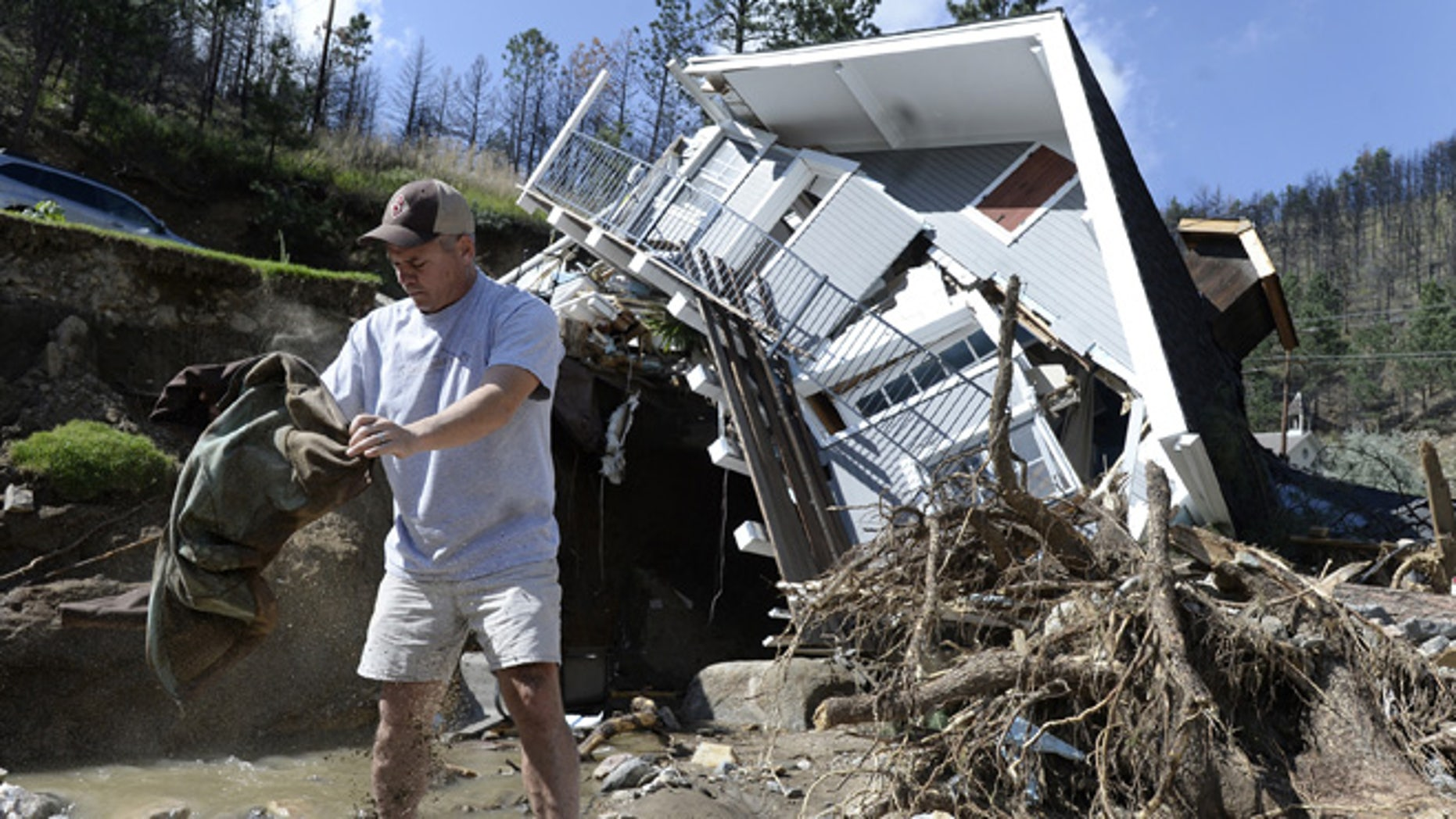 Sept. 19, 2013: In this photo, Sean McCroskey pulls his wife Meg's jacket out of the debris in the river in front of their destroyed home on Gold Run Road in Boulder County, Colo. State highway crews and National Guard troops worked Sunday, Sept. 22, to repair highways to Colorado mountain towns cut off by the unprecedented flooding.