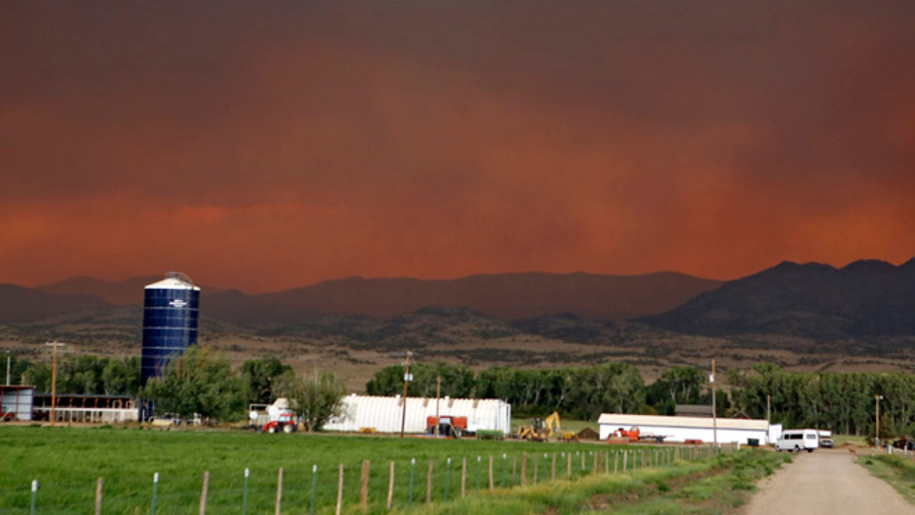 June 21, 2013: The smoke in the sky over a ranch near South Fork, Colo., glows red from a wildfire that is threatening the town. South Fork was evacuated Friday as the fire approaches from the west.