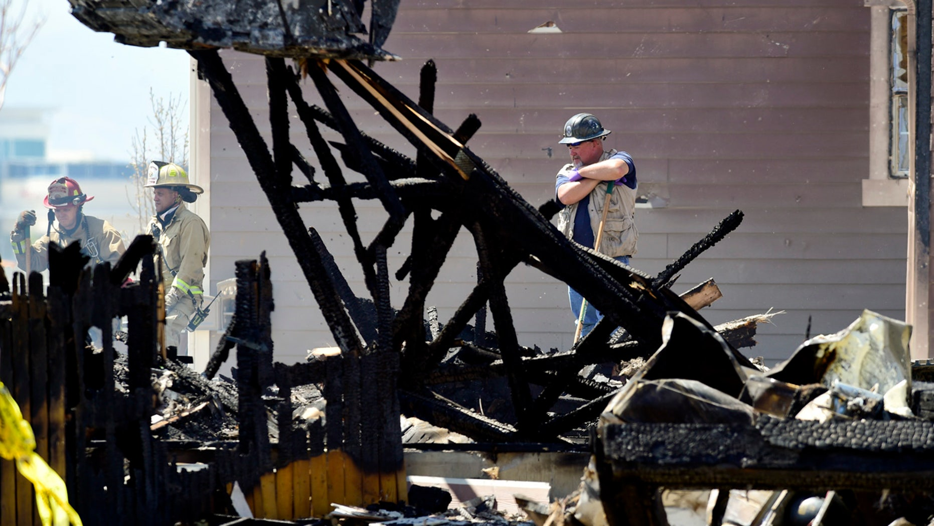 In this April 18, 2017, photo, investigators stand by as debris is removed from a house that was destroyed in a deadly explosion in Firestone, Colo., on April 17,