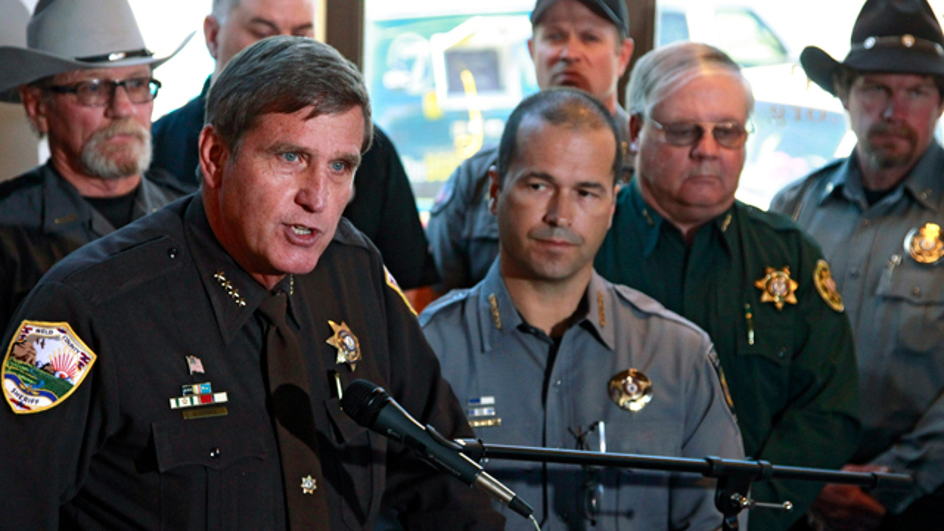 May 17 2013: Weld County, Colo., Sheriff John Cooke, left, with El Paso County Sheriff Terry Maketa, center right, and other sheriffs standing behind him, speaks during a news conference at which he announced that 54 Colorado sheriffs are filing a federal civil lawsuit against two gun control bills passed by the Colorado Legislature, in Denver.