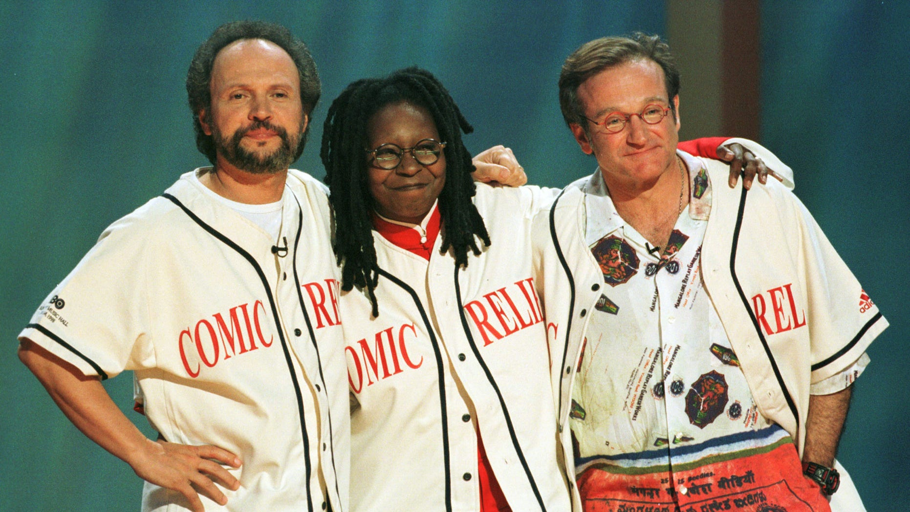 Comedians Robin Williams (R), Billy Crystal (L) and Whoopi Goldberg share a hug on the stage at the end of Comic Relief 8.