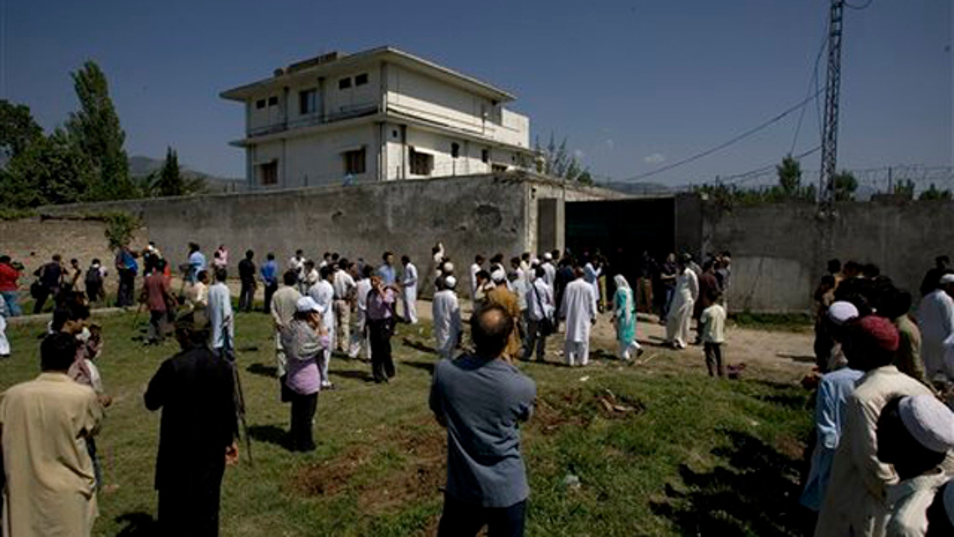Local people and media gather outside the perimeter of the compound where Usama bin Laden was caught and killed in Abbottabad, Pakistan, May 3.