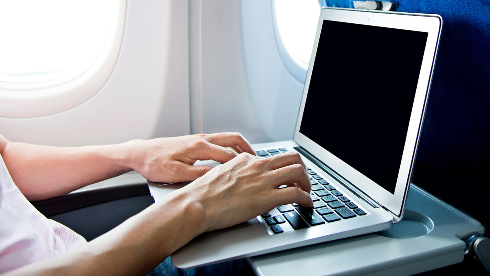 Man using laptop computer on airplane.