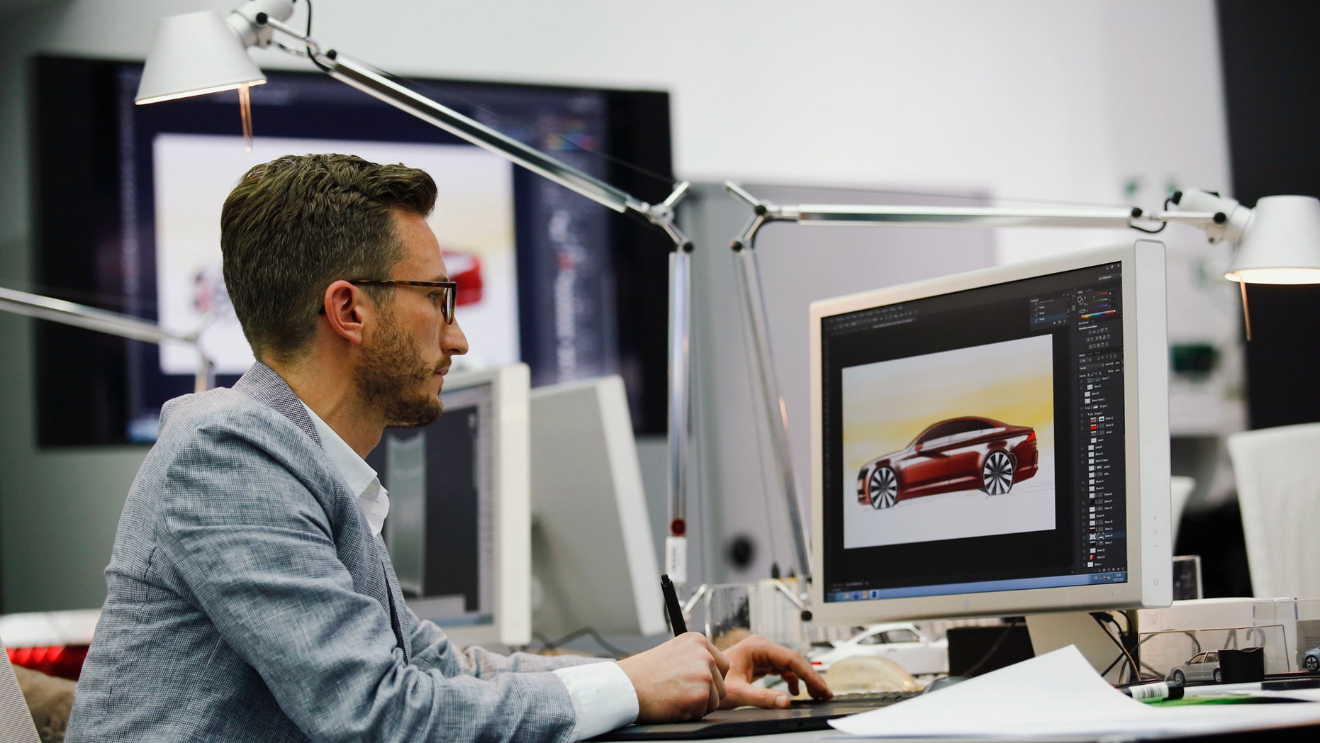 File photo: A man works in a showcase design studio at the fringes of a launch ceremony presenting the new Volkswagen Passat at the Volkswagen Design Center in Potsdam July 3, 2014. (REUTERS/Thomas Peter GERMANY - Tags: TRANSPORT BUSINESS)