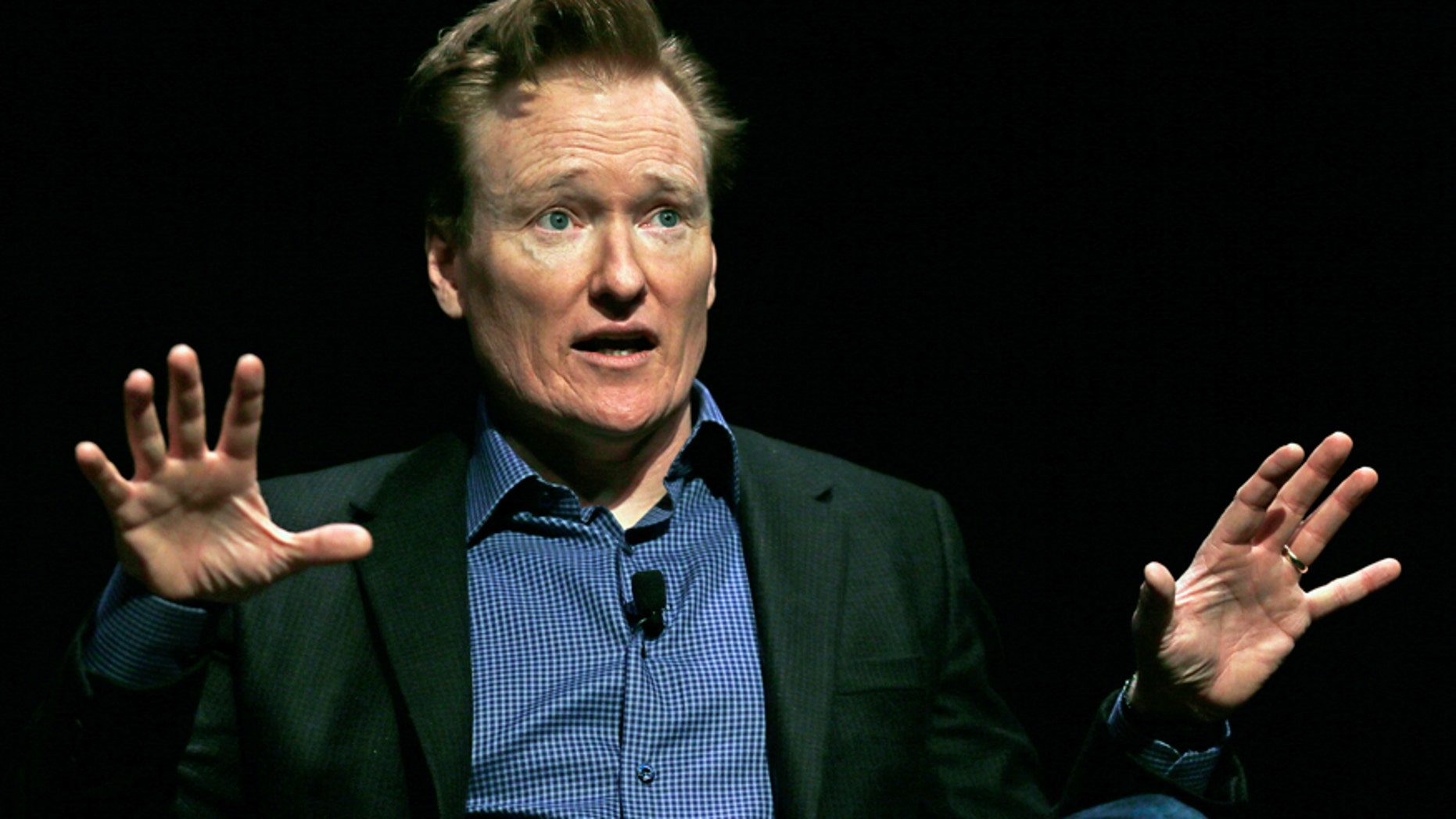 In this Feb. 12, 2016 file photo television host Conan O'Brien gestures to the audience at Sanders Theatre on the campus of Harvard University in Cambridge. O'Brien is vigorously defending himself from plagiarism allegations by a writer who accused him of ripping off punchlines about Caitlyn Jenner, Tom Brady and the Washington Monument.