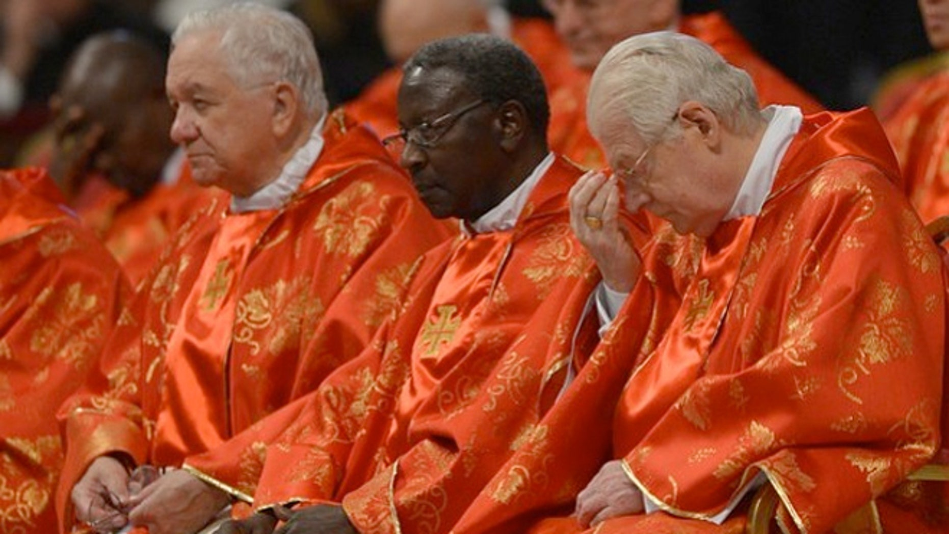 Senegalese cardinal Theodore-Adrien Sarr (C) and Italian cardinal Angelo Scola (R) were served simple meals during their deliberation over the next Pope.