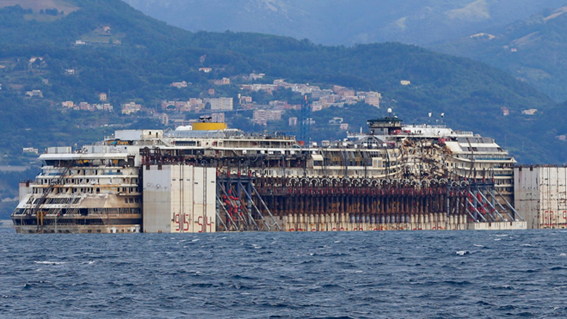 July 27, 2014: The wreck of the Costa Concordia cruise ship is towed by tugboats towards Genoa's harbor, Italy.