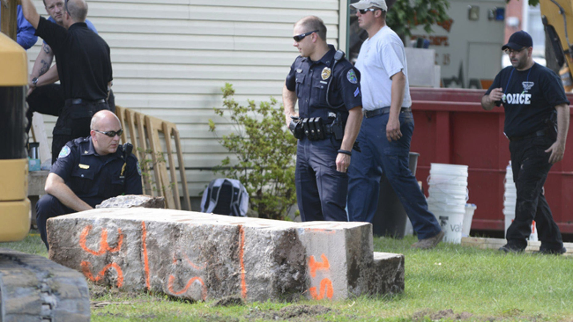 Police officers look over a slab of concrete pulled out of the basement of a home in Milton, Pa.