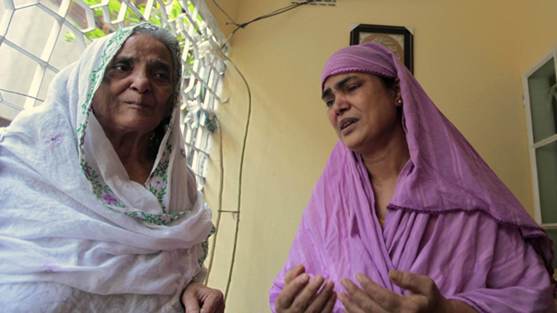 Oct. 18, 2012: Grandmother, left, and aunt of Bangladeshi Quazi Mohammad Rezwanul Ahsan Nafis weep in his home in the Jatrabari neighborhood in north Dhaka, Bangladesh.