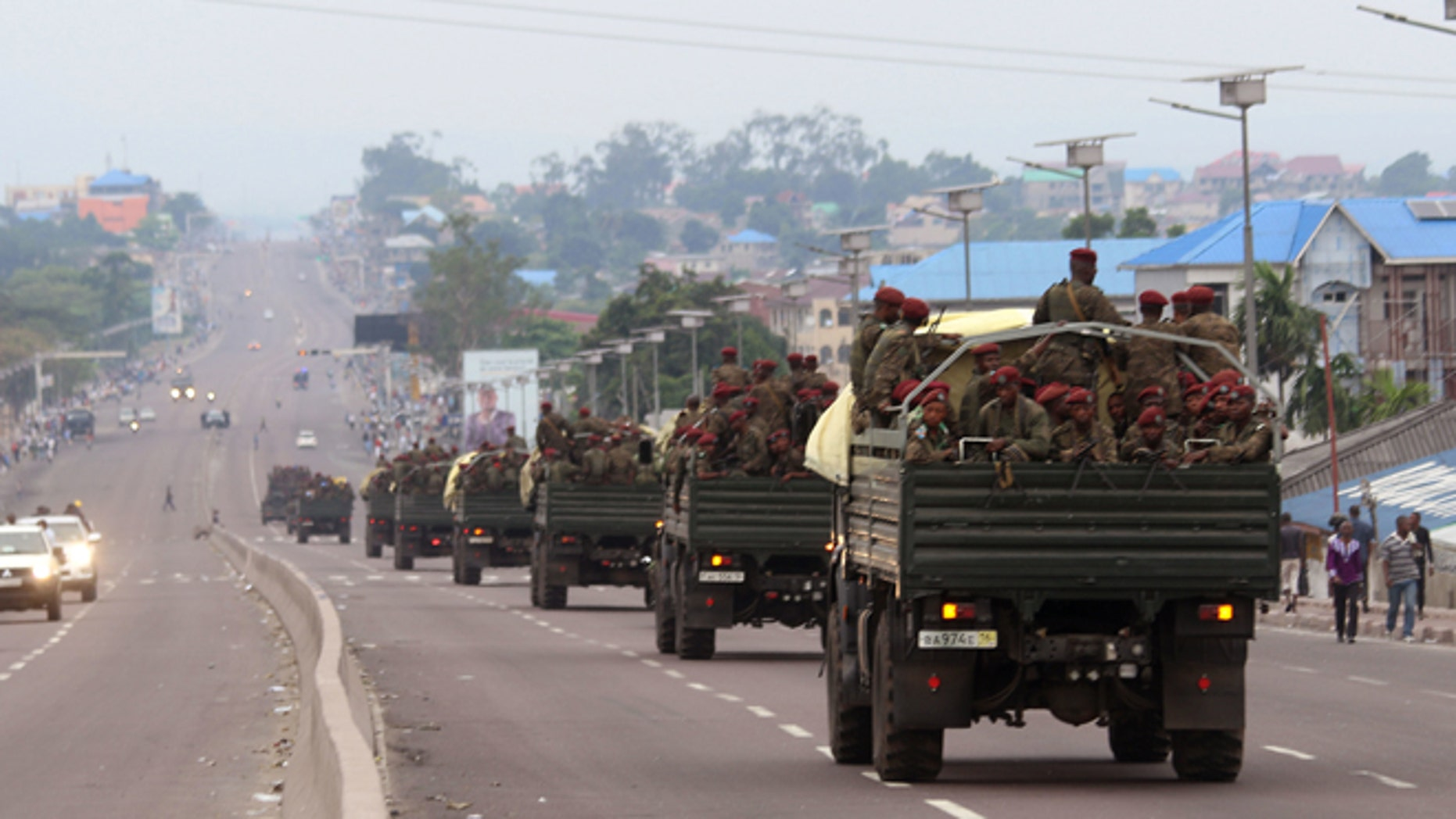 Congo military trucks carrying Congolese troops drive in a main street after violence erupted due to the delay of the presidential elections in Kinshasa, Democratic Republic of Congo, Tuesday, Sept. 20, 2016.