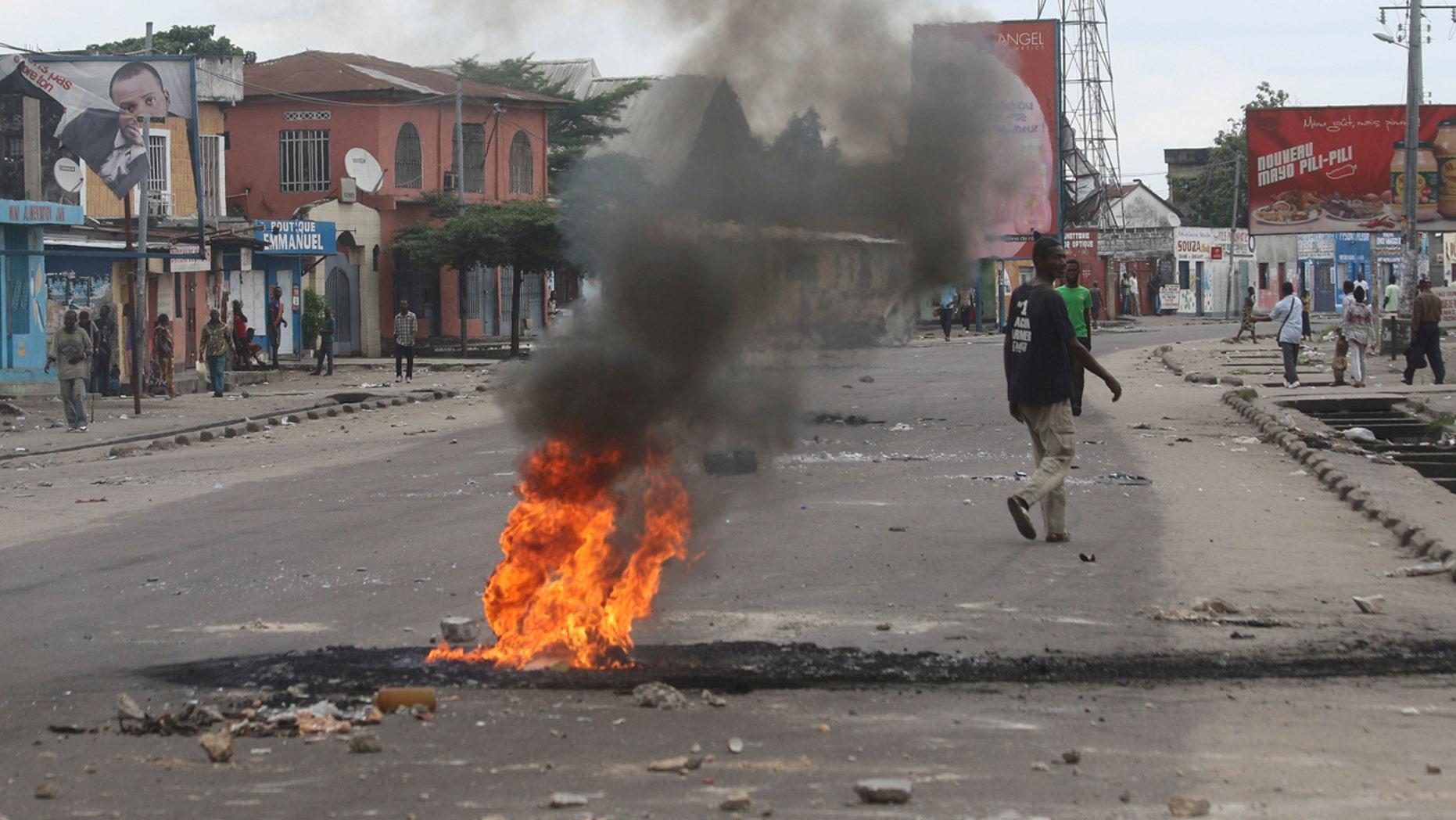 People walk near burning debris during protests in Kinshasa, Democratic Republic of Congo, Tuesday, Dec. 20, 2016.