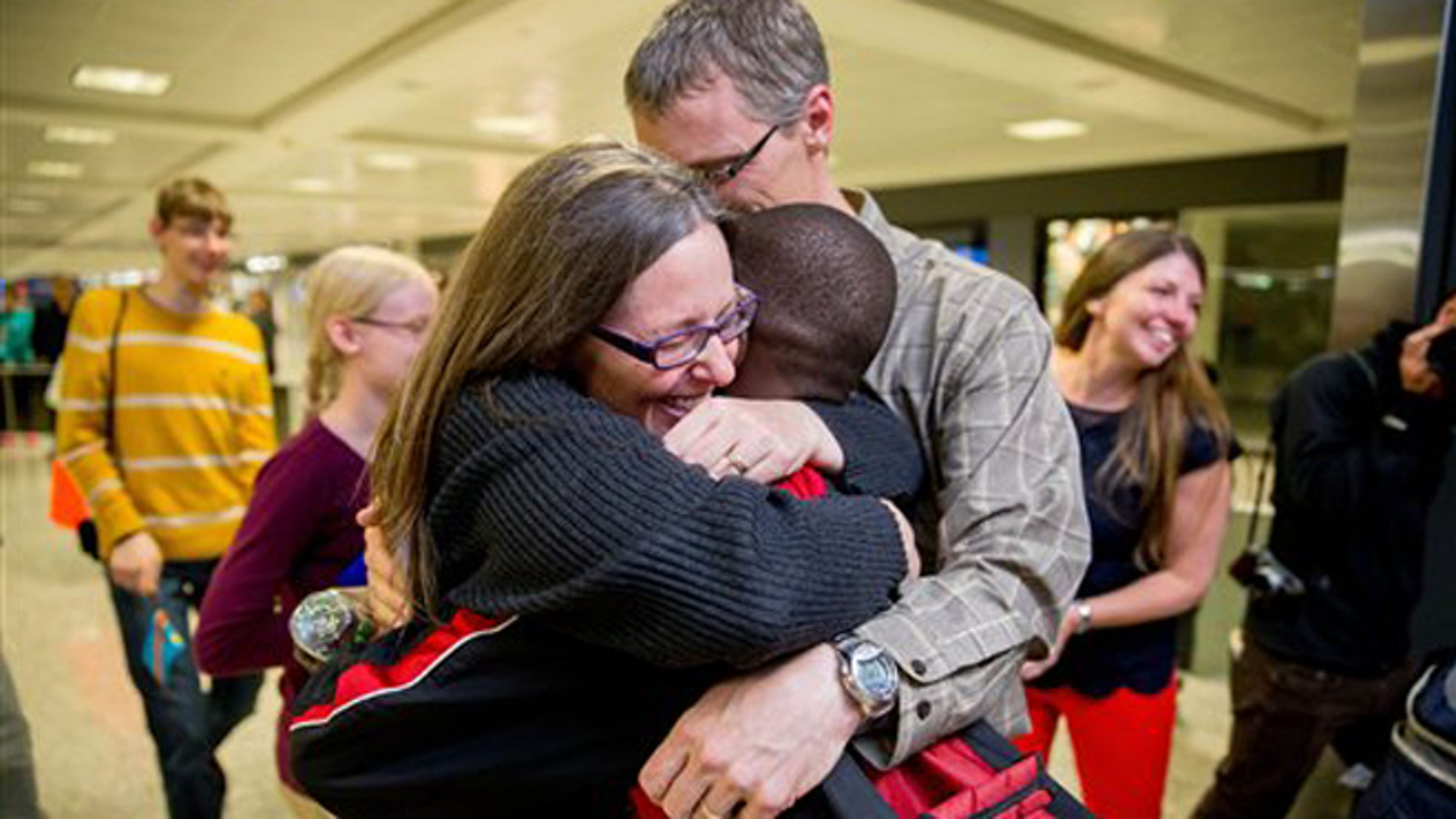 Nov. 11, 2015: Jennifer and Eric Sands of Illinois hug their adopted son Issaac, 12, as he arrives from the Congo at Dulles International Airport.