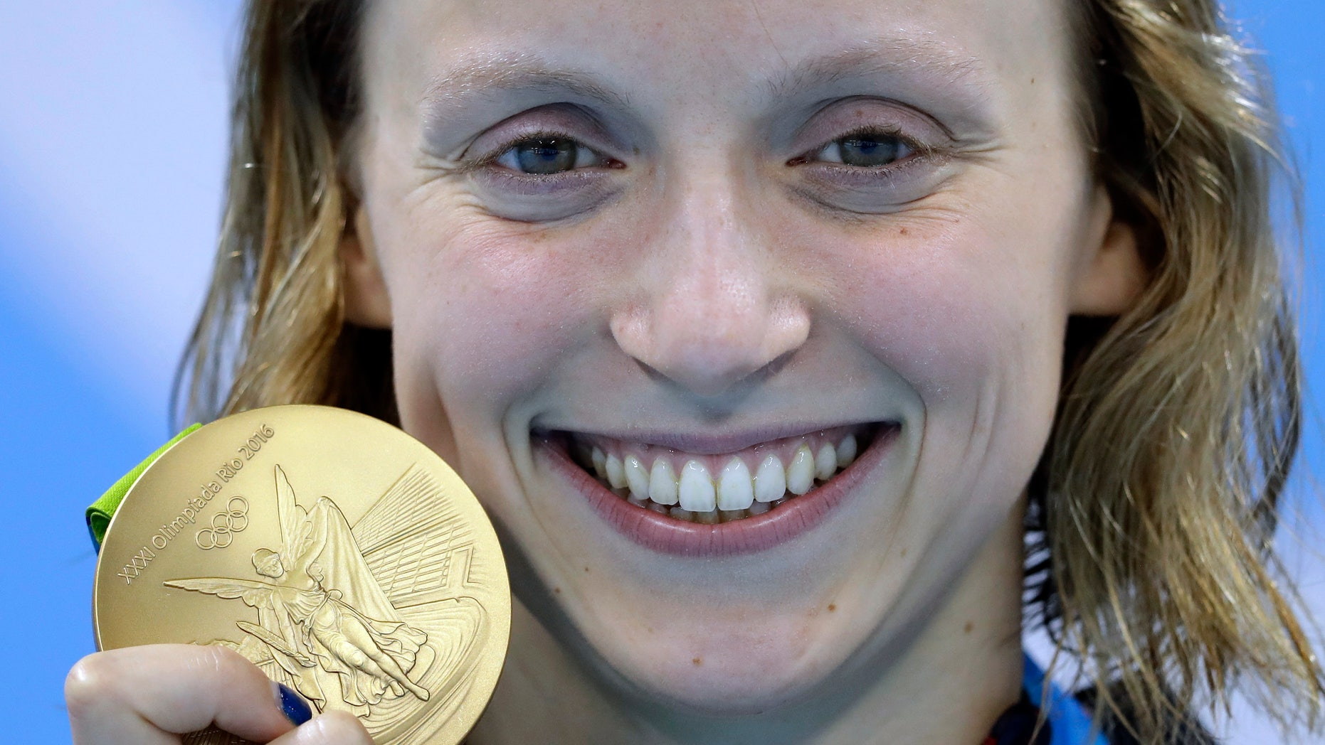 Aug. 12, 2016: United States' Katie Ledecky shows off her gold medal in the women's 800-meter freestyle medals ceremony during the swimming competitions at the 2016 Summer Olympics in Rio de Janeiro, Brazil.