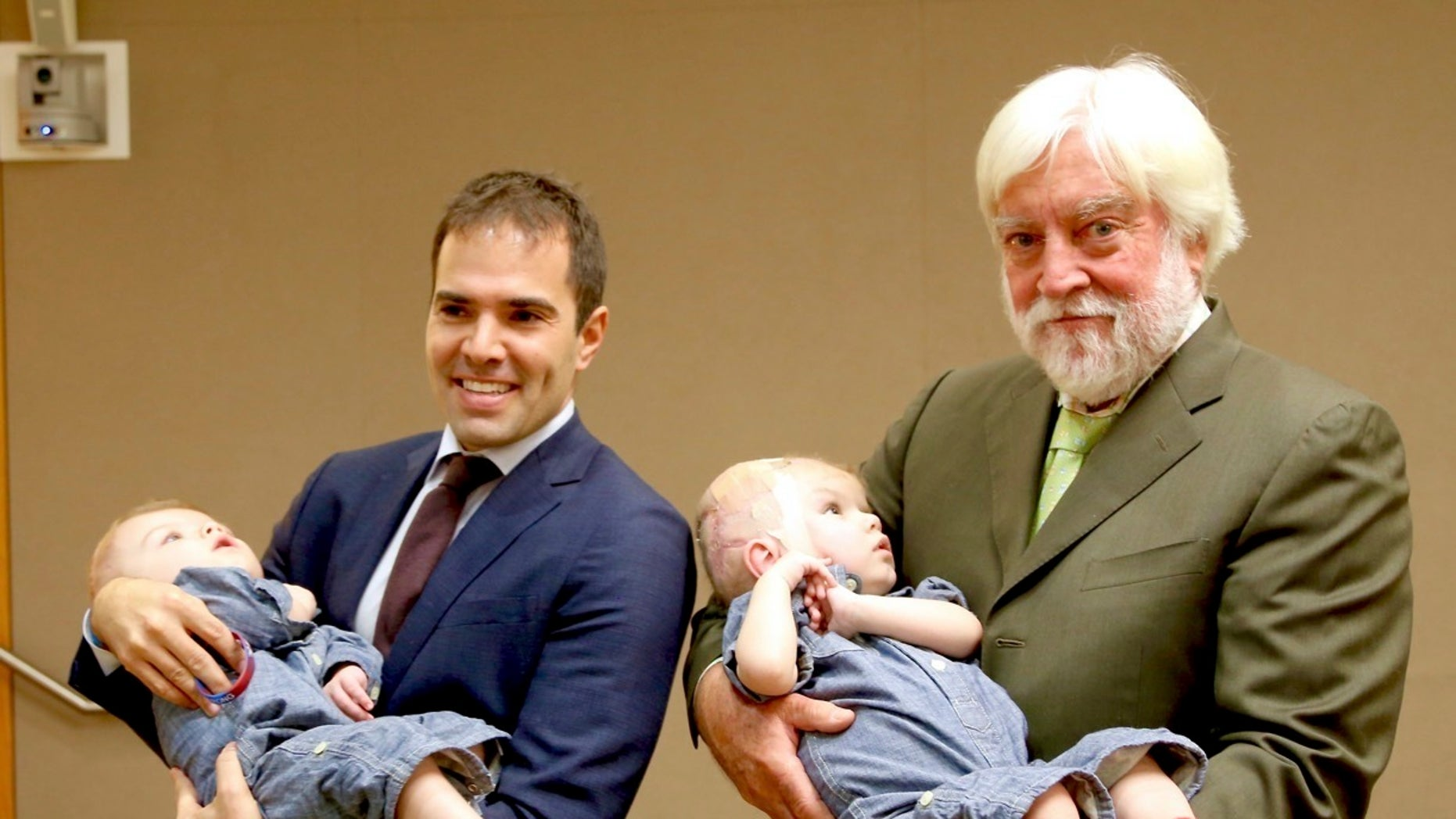 This photo provided by Montefiore Hospital shows, from left, Dr. Oren Tepper and  Dr.  James Goodrich holding a pair of formerly conjoined twins, Jadon, left and Anias in New York.  Jadon and Anias were separated in a 20-hour procedure at New York City's Montefiore Medical Center on Oct. 13 and 14, 2016. The hospital says they have been transferred to Blythedale Children's Hospital in suburban Westchester, where they will receive specialized rehabilitation care.  (Montefiore Hospital via AP)