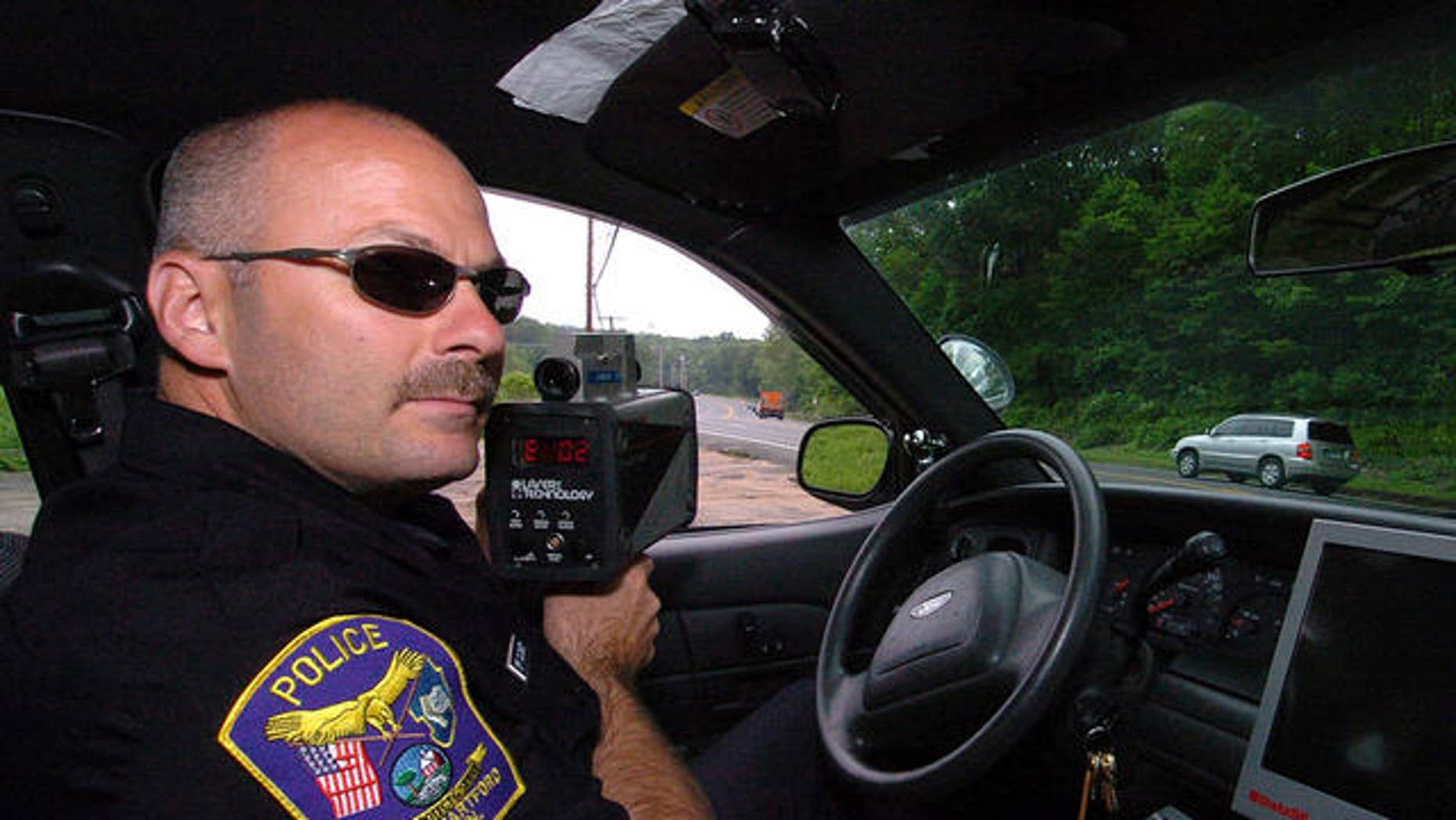 ** ADVANCE FOR WEEKEND, JULY 1-2  ** West Hartford Police Officer Kerry Cloukey uses a laser unit to detect speeders on Route 44 on Avon Mountain in West Hartford, Conn., Thursday, June 22, 2006.  Starting July 1, 2006, a new Connecticut law adds $10 to every ticket issued for speeding, failure to yield, making an illegal turn and dozens of other moving violations.  (AP Photo/Jessica Hill)