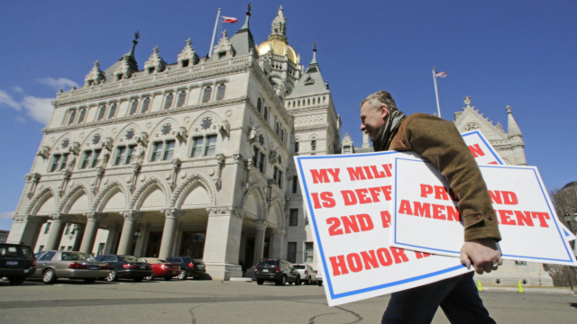 April 3, 2013: Jody Winslow, of Farmington, Conn., carries signs regarding the second amendment of the U.S. Constitution as he heads back to the Capitol in Hartford, Conn.