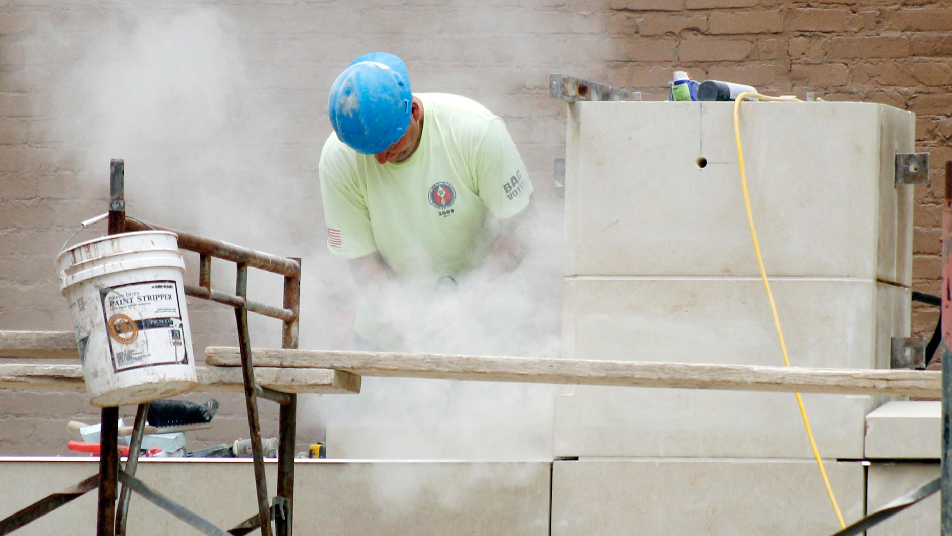 In this July 21, 2011 photo, a workman stands in a cloud of dust as he grinds block for fitment at a construction site at Point Park College in downtown Pittsburgh.