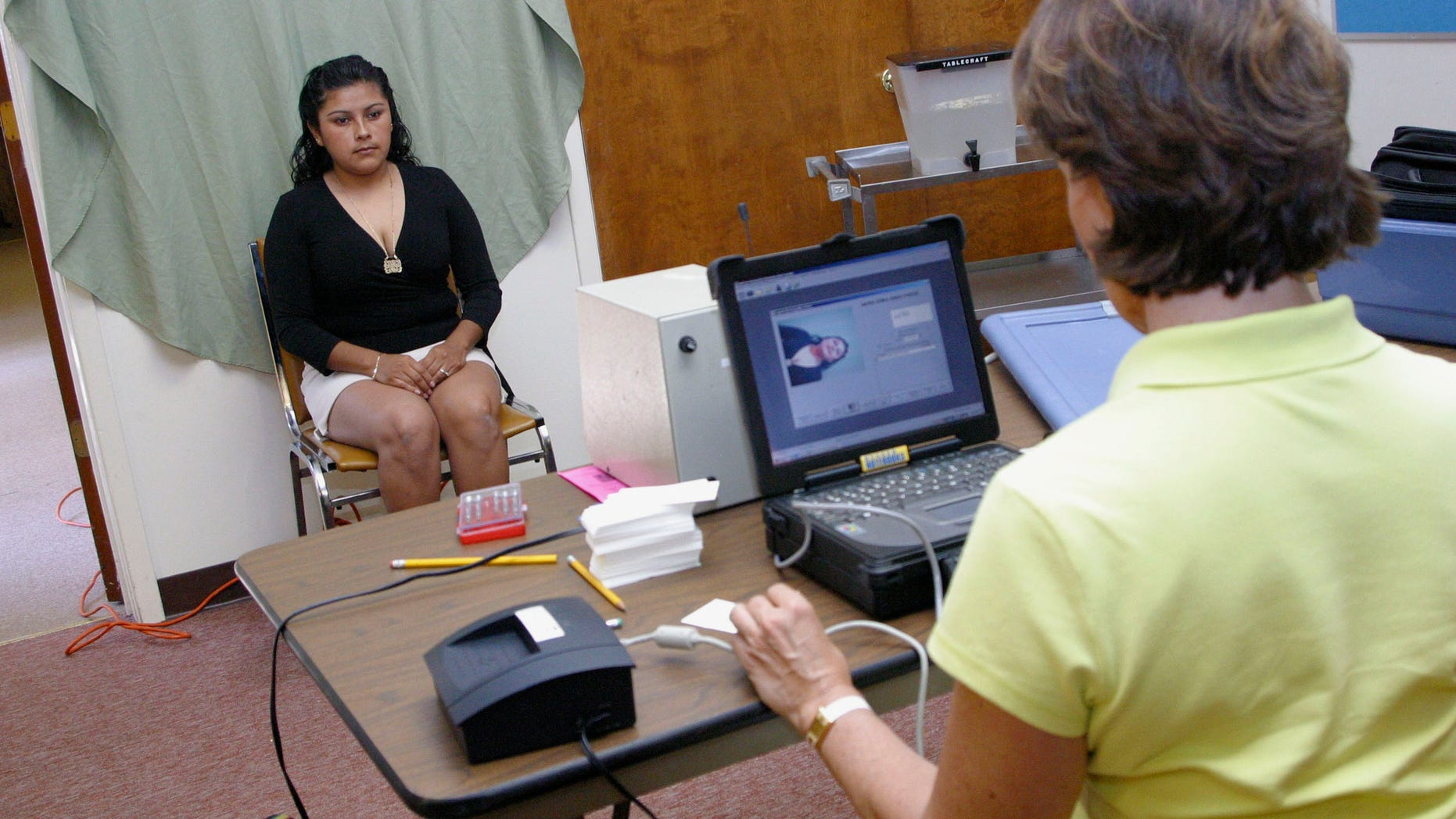 """LONGVIEW, TX-July 24: Erika Tidmore, Mexican citizens married to an American, has a photograph take during the application process for the """"Matricula Consular"""" card, an identification issued to legitimate Mexican citizens living outside of Mexico. A half dozens Mexican Consulate officials, from Dallas, Texas established what they called a """"mobile consulate"""" at the Wesley-McCabe United Methodist Church in Longview, Texas, on Saturday, July 24, to process applicants 450 Mexican citizens in the Northeast Texas town. The ID cards assist local and state Texas officials to recognize legitimate Mexican residents in the United States. Applicants for the """"Matricula Consular"""" cards had to prove legal residence in the United States to receive the card.  Photo by Mario Villafuerte/Getty Images"""
