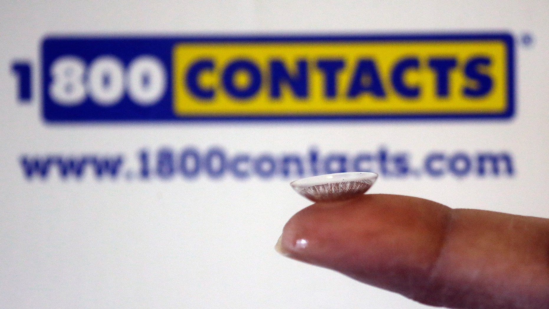 In this file photo, a contact lens is displayed in front of a 1-800-Contacts shipping box in Salt Lake City.