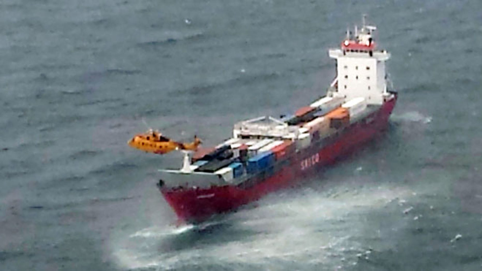Oct. 17, 2014: A Canadian Coast Guard helicopter flies near a Russian container ship, carrying hundreds of tons of fuel drifting without power in rough seas off British Columbia's northern coast