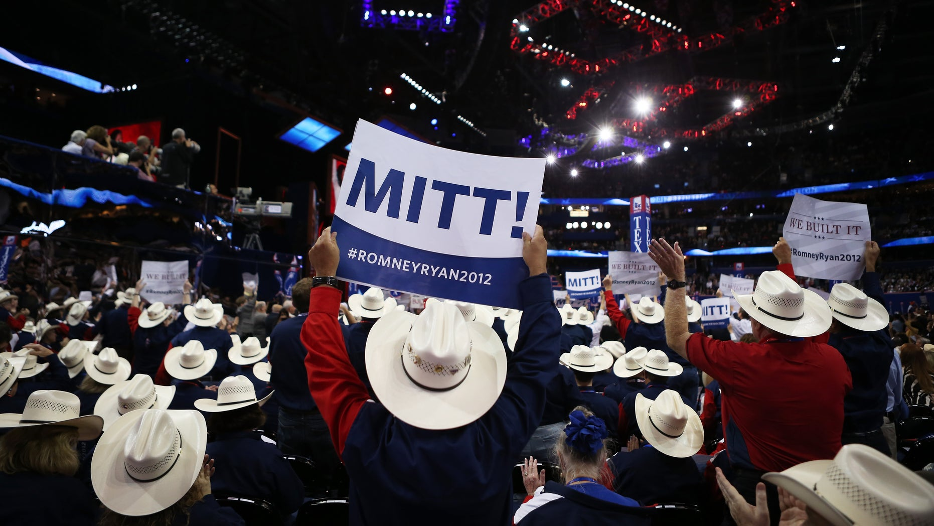 """TAMPA, FL - AUGUST 28:  People from the Texas delegation hold signs that say  """"Mitt!"""" during the Republican National Convention at the Tampa Bay Times Forum on August 28, 2012 in Tampa, Florida. Today is the first full session of the RNC after the start was delayed due to Tropical Storm Isaac.  (Photo by Chip Somodevilla/Getty Images)"""