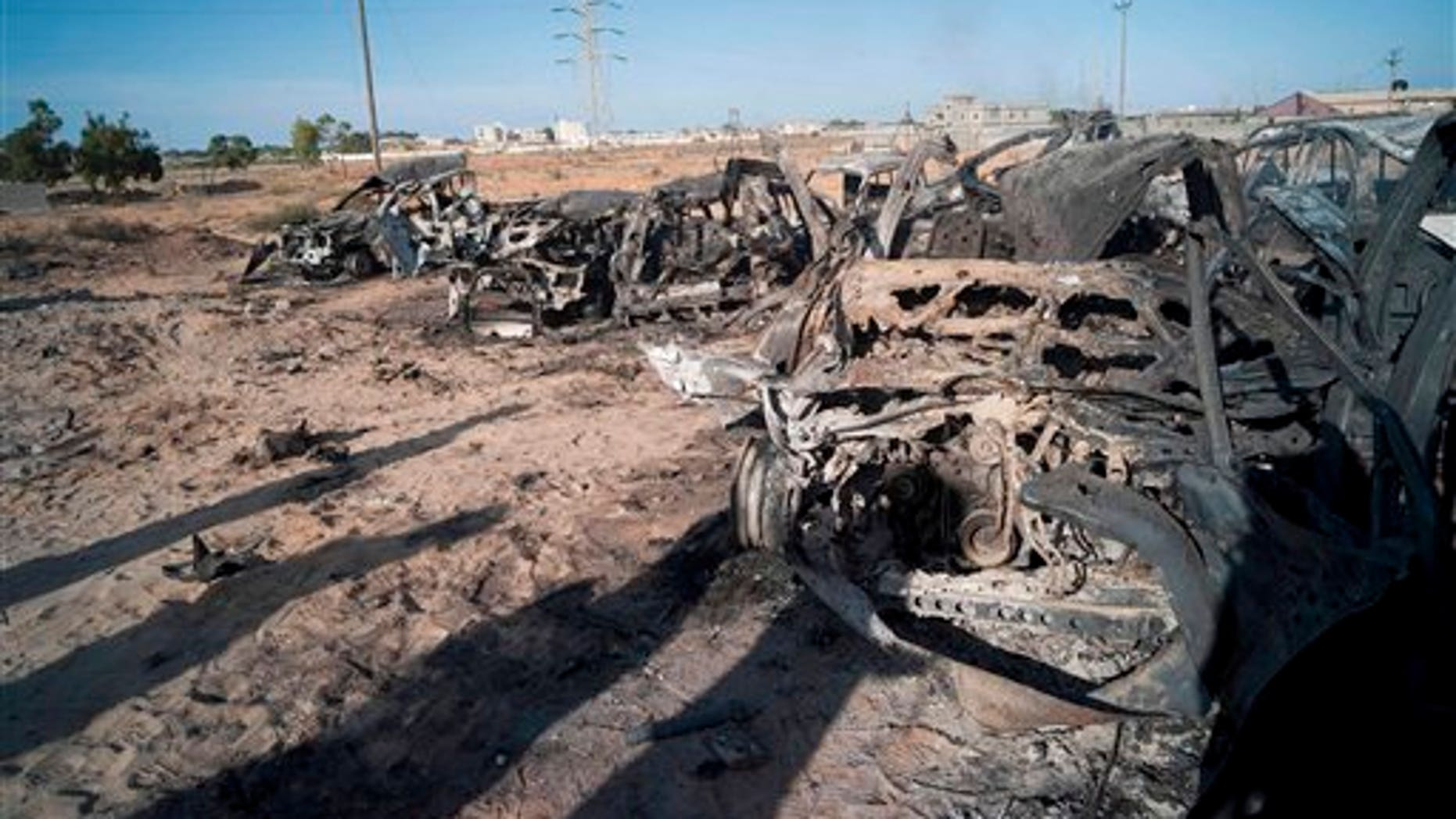 Oct. 20: The wreckage of burnt vehicles from a convoy of pro-Qaddafi fighters trying to flee the town of Sirte, Lybia, lie on the edge of town.