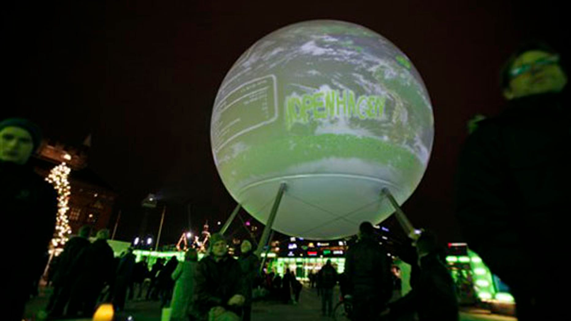 A globe is projected as people are seen in Town Hall Square on the opening day of the Climate Conference in Copenhagen Dec. 7. (AP Photo)