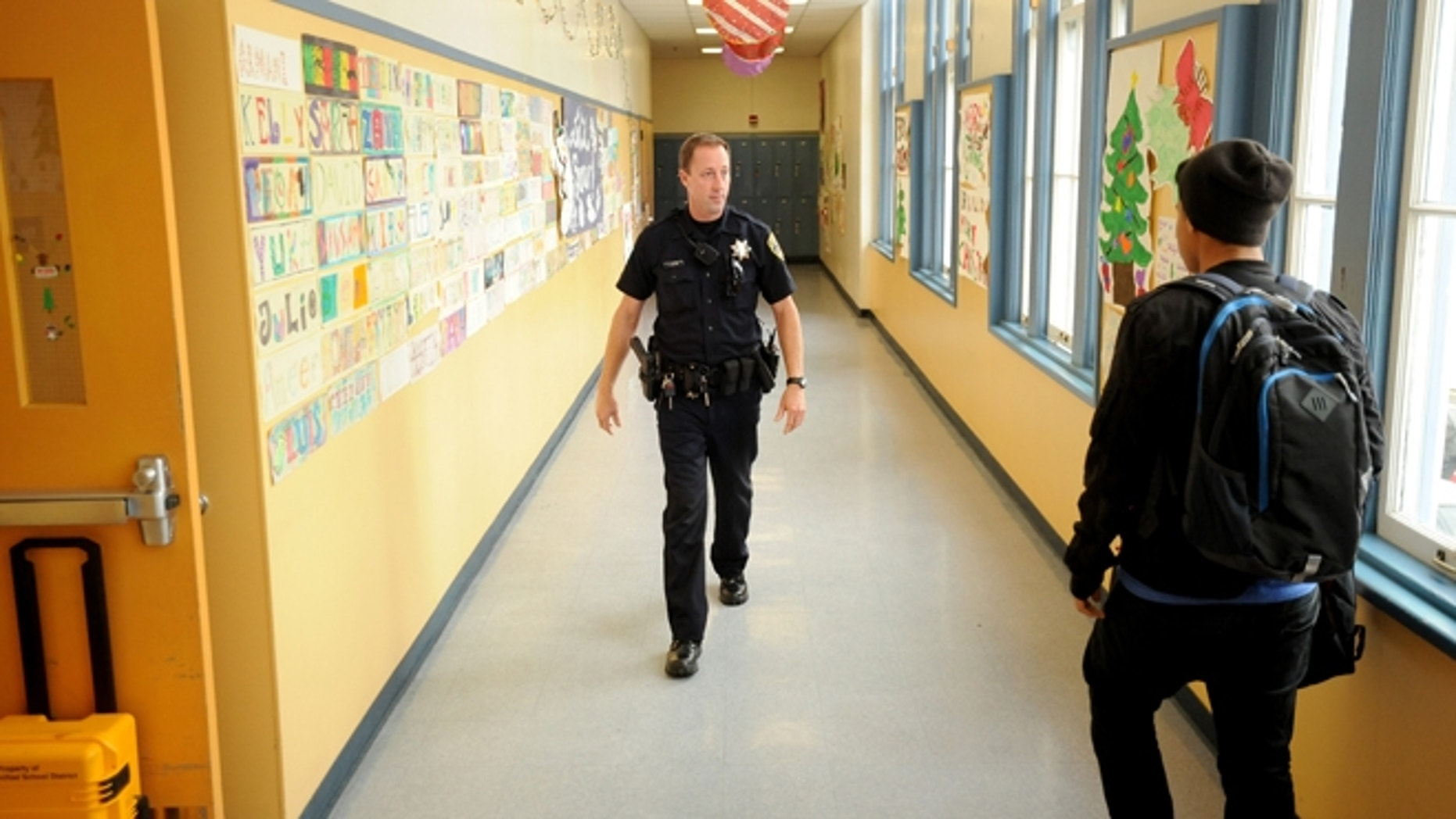 Oakland Calif. Police Officer Rick Moore patrols Oakland Technical High School. (AP Photo/Noah Berger)