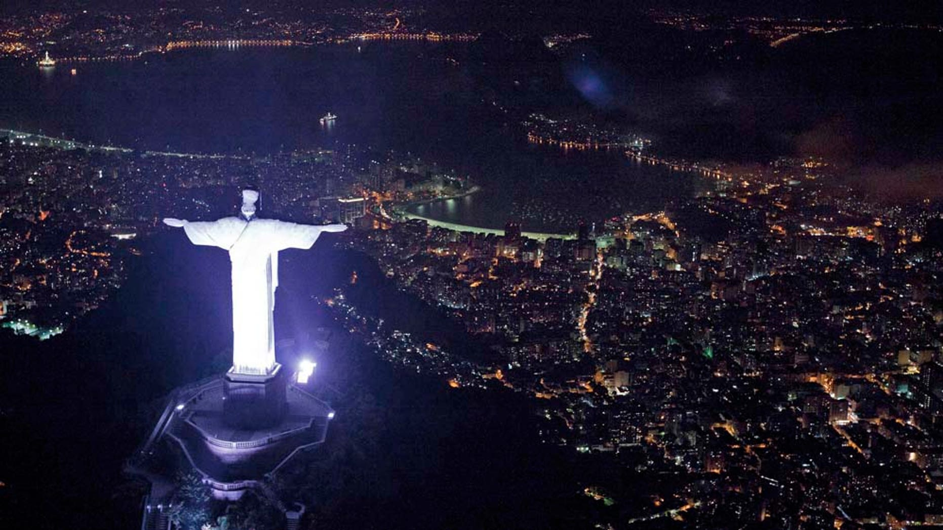"""An aerial view of the iconic Christ the Redeemer statue before the lights that illuminate the statue are switched off to observe an hour of voluntary darkness for the global """"Earth Hour"""" campaign, in Rio de Janeiro, Brazil, Saturday March 26, 2011.  An estimated 1,000 landmarks' lights were turned off worldwide for 60 minutes at 8:30 p.m. local time, as a symbolic act to raise awareness about climate change and to make people aware of everyday energy use.  (AP Photo/Felipe Dana)"""