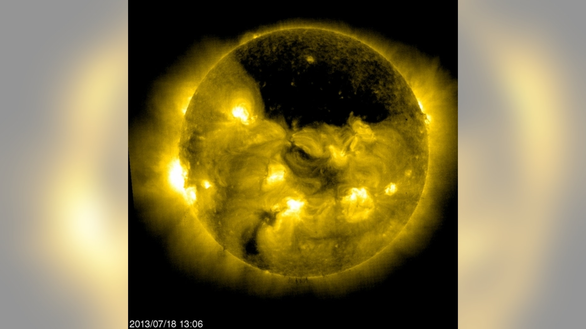 The European Space Agency/NASA Solar and Heliospheric Observatory, or SOHO, captured this image of a gigantic coronal hole hovering over the sun's north pole on July 18, 2013, at 9:06 a.m. EDT.