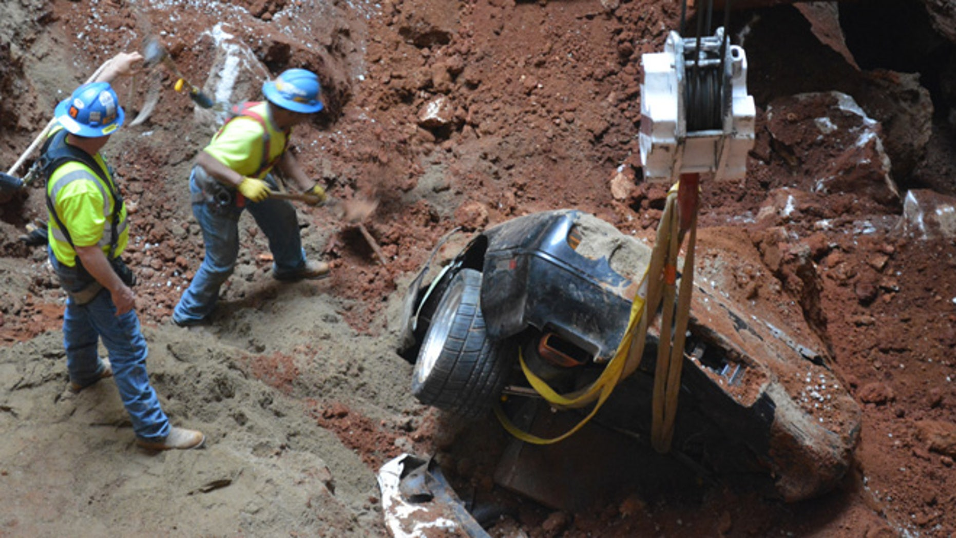 In this undated photo provided by the National Corvette Museum, workers pull out a car from a sinkhole at the National Corvette Museum, in Bowling Green, Ky.