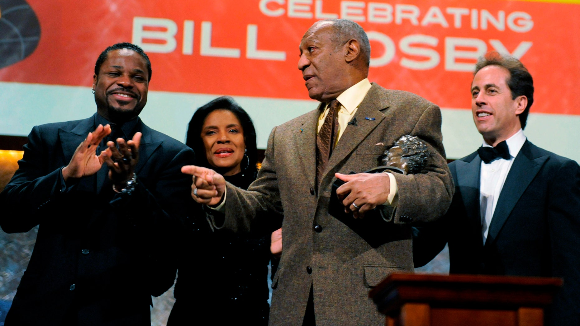 Comedian, actor, author and musician Bill Cosby (2nd R) cradles his Mark Twain award in his arm as he jokes with cast members (from L to R) actor Malcolm-Jamal Warner, actress Phylicia Rashad and comedian Jerry Seinfeld at the conclusion of the Kennedy Center For the Performing Arts' fete for Cosby, where he was honored with their annual Mark Twain Prize for American Humor, in Washington, October 26, 2009.  REUTERS/Mike Theiler (UNITED STATES ENTERTAINMENT)