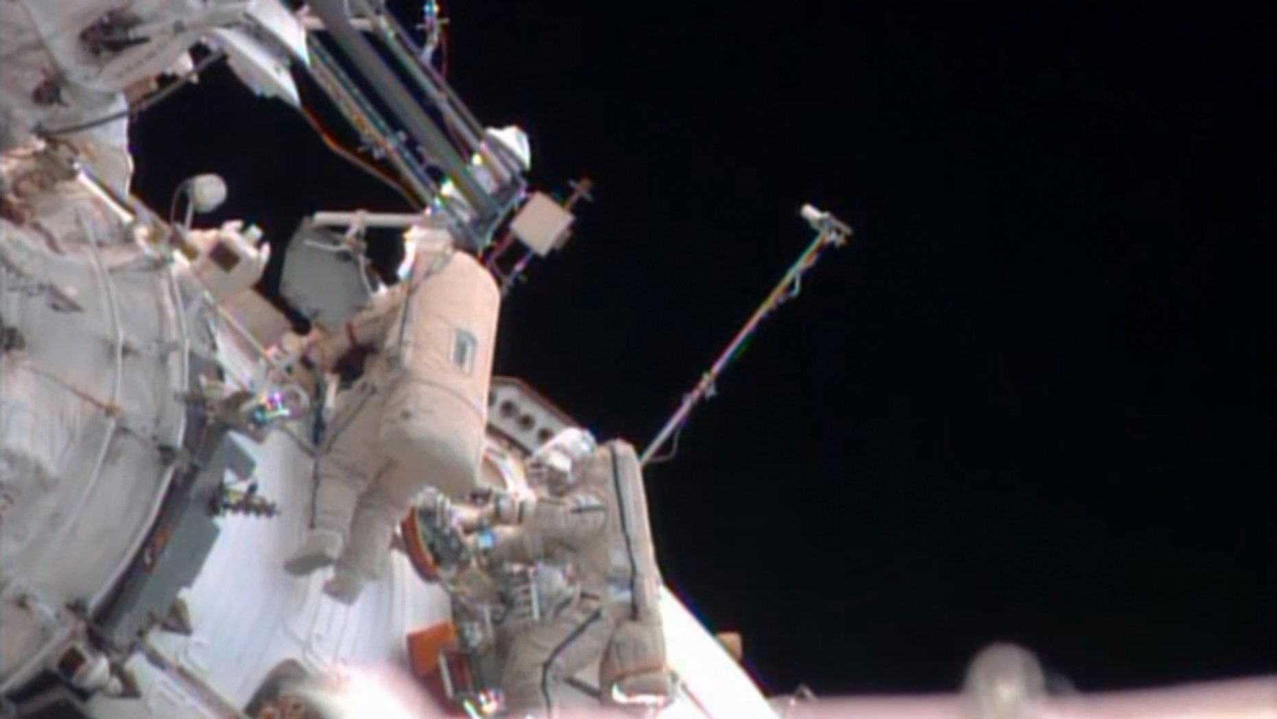 Russian cosmonauts Pavel Vinogradov, left, and Roman Romanenko perform a spacewalk outside the International Space Station to gather old science experiments and install new ones, and replace a navigation device.
