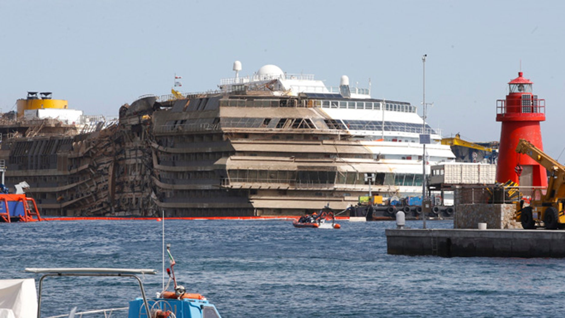 """Sept. 17, 2013: The cruise liner Costa Concordia is seen at the end of the """"parbuckling"""" operation outside Giglio harbor. Salvage crews completed raising the wreck of the Costa Concordia in the early hours of Tuesday morning after a 19-hour-long operation on the Italian island of Giglio where the huge cruise liner capsized in January last year."""