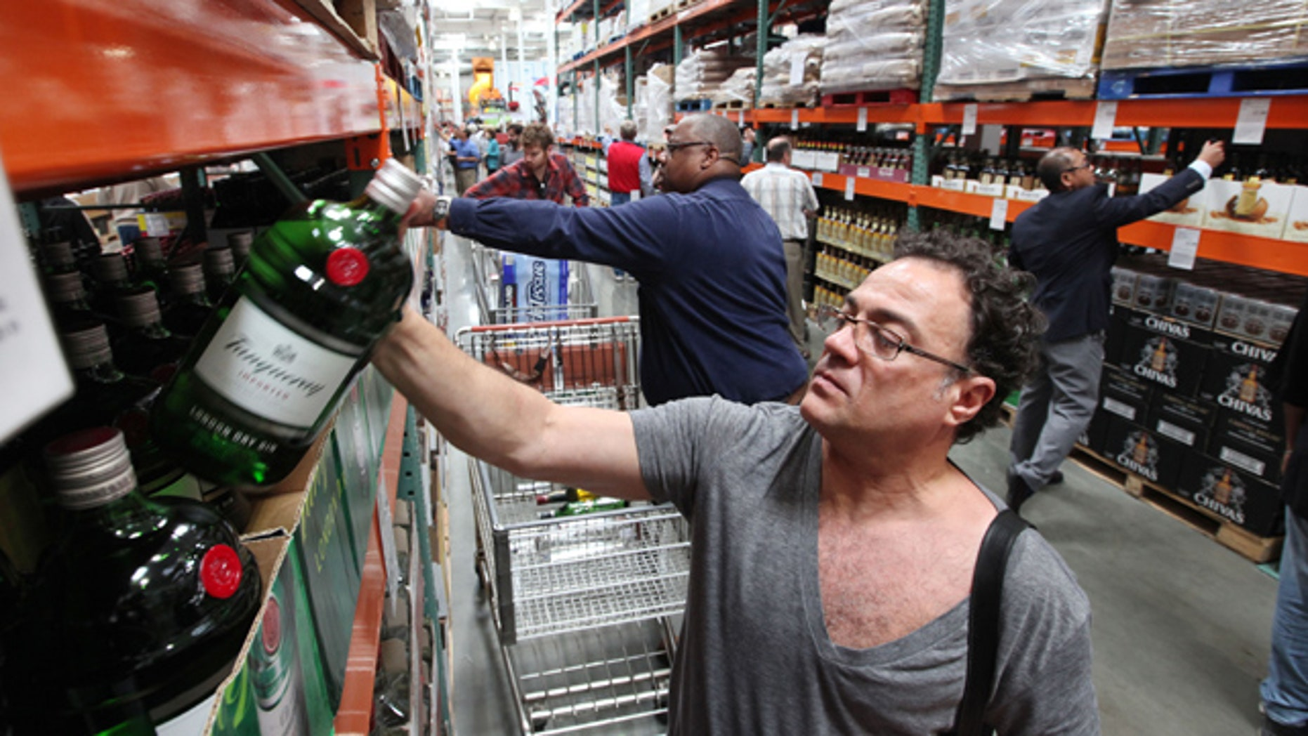 June 1, 2012: Al Bragalone looks at a bottle of gin as shoppers fill a new liquor aisle at a Costco warehouse store in Seattle, not far from the company's store in Bellingham, Wash., where some shoppers want American-only hours amid a crush of Canadian consumers. (AP)