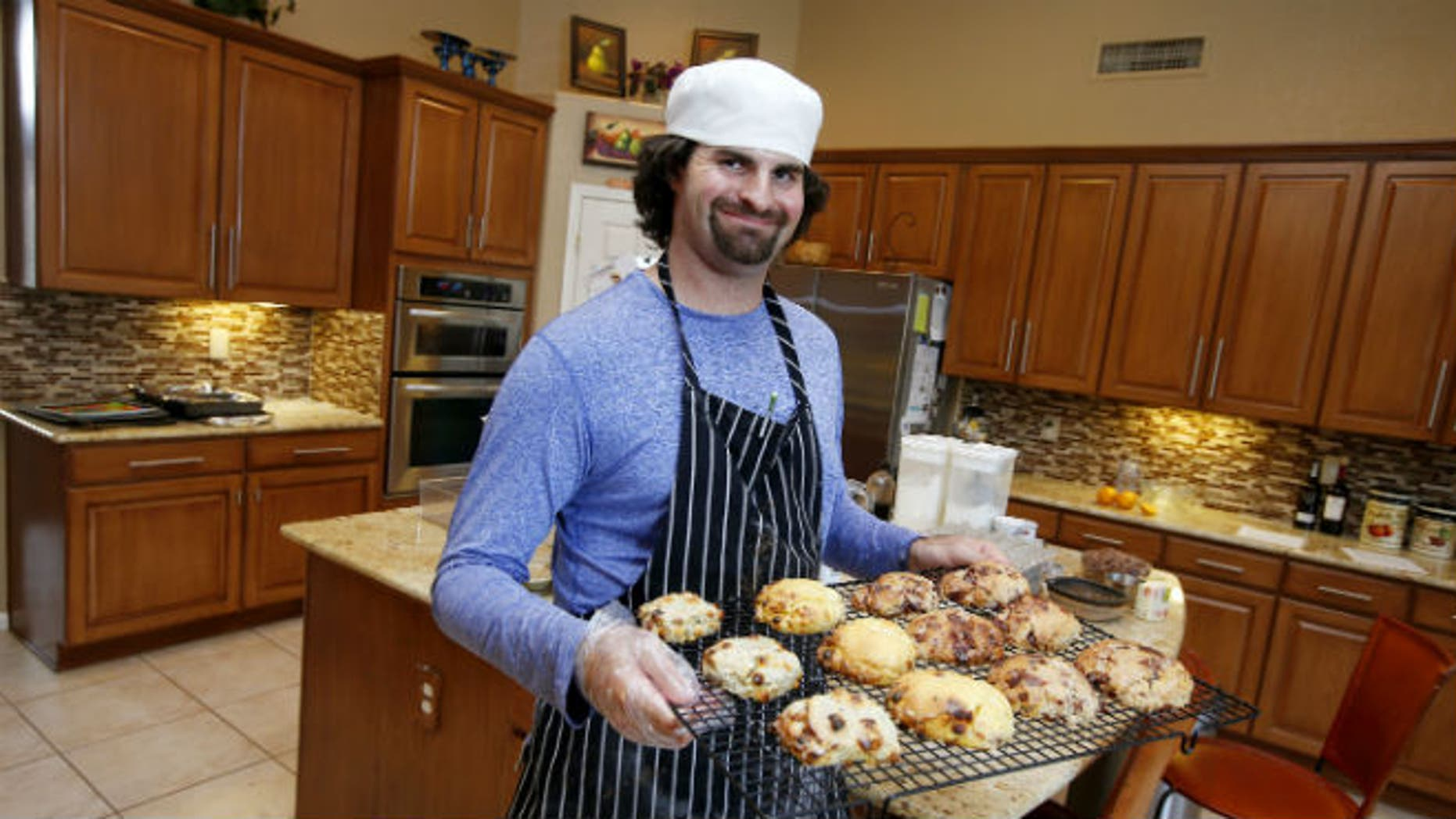In this July 15, 2014 photo, Matt Cottle, owner of Stuttering King Bakery, smiles as he holds a tray of his scones in his parents' kitchen in Scottsdale, Ariz. (AP Photo/Ross D. Franklin)