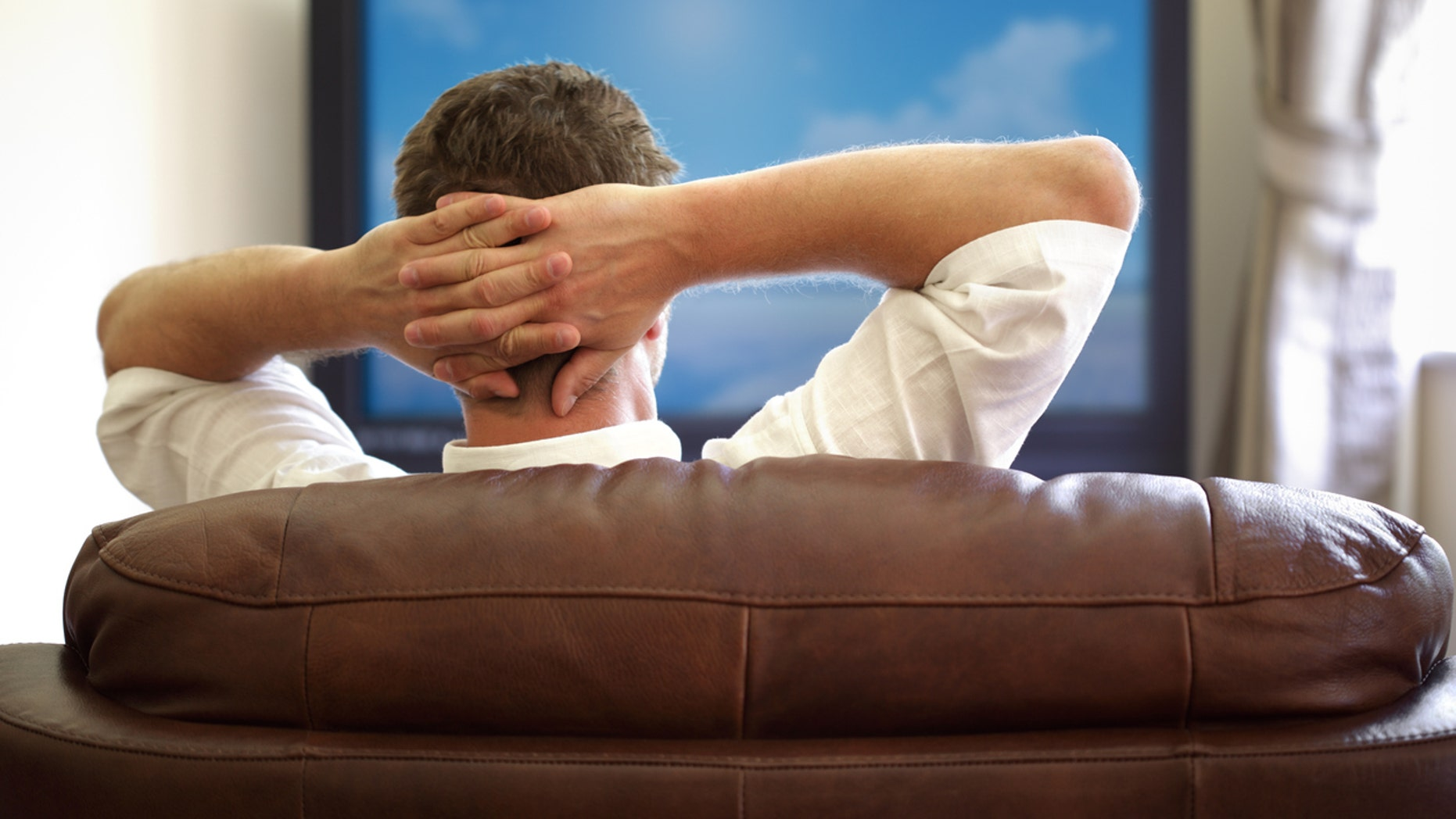 Man sitting on a sofa watching tv with hands folded behind his headPlease see similar picture from my portfolio: