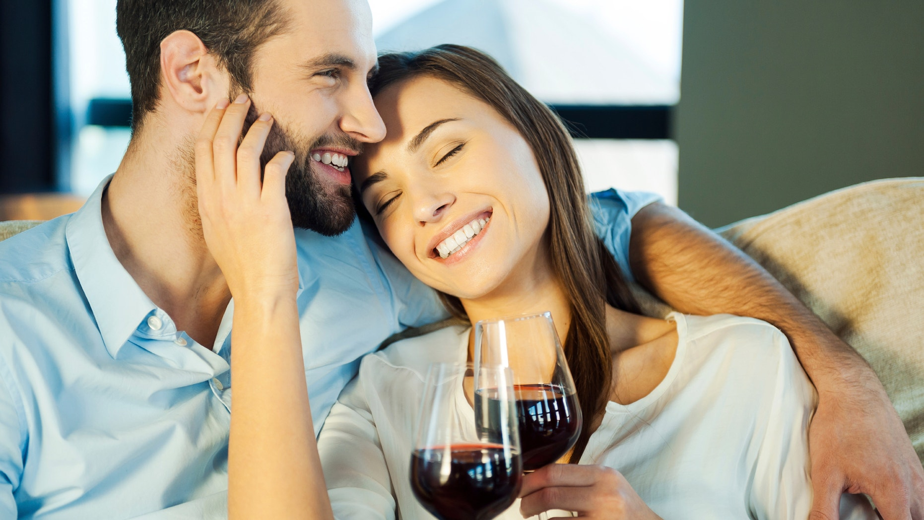 Love is a great feeling. Beautiful young loving couple sitting close to each other and drinking red wine