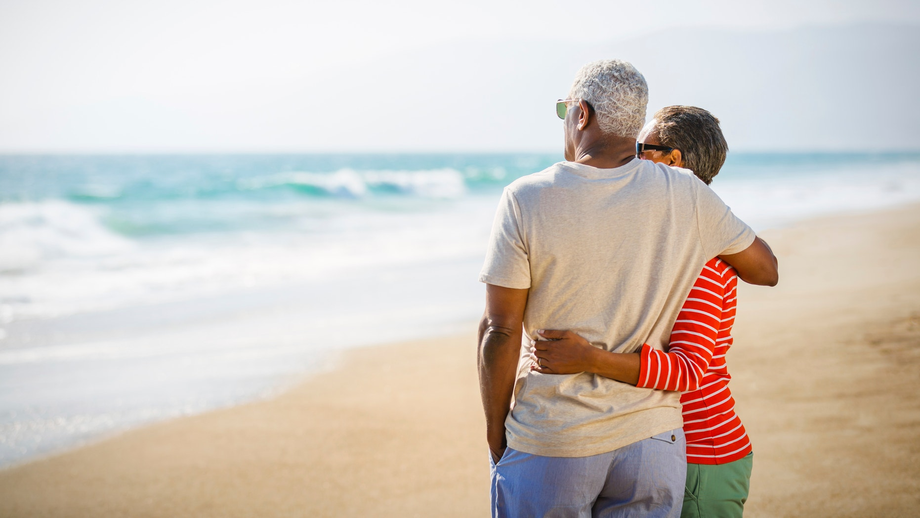 Senior African American couple embracing at sandy beach.