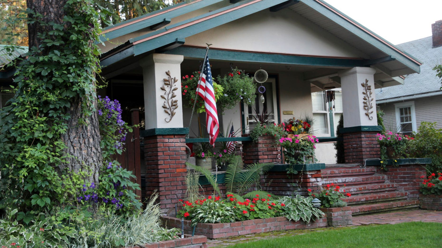 A Craftsman house displays the flag and flowers in front.