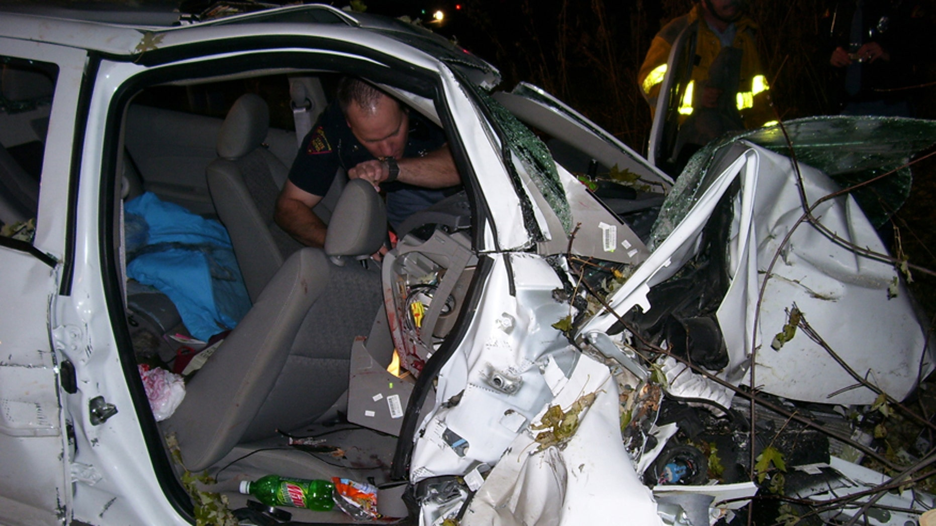 In this Oct. 24, 2006 photo provided by the St. Croix County Sheriff's Office, police investigate the wreckage of a 2005 Chevrolet Cobalt that crashed in St. Croix County, killing Natasha Weigel, 18, and Amy Lynn Rademaker, 15, and injuring the 17-year-old driver, Megan Ungar-Kerns. The vehicle's ignition was found in the accessory position and the air bags didnt deploy. General Motors recent recall of 2.6 million small cars, including the 2005 Cobalt, has shed light on an unsettling fact: Air bags might not always deploy when drivers _ and federal regulators _ expect them to. (AP Photo/St. Croix County Sheriff's Office)