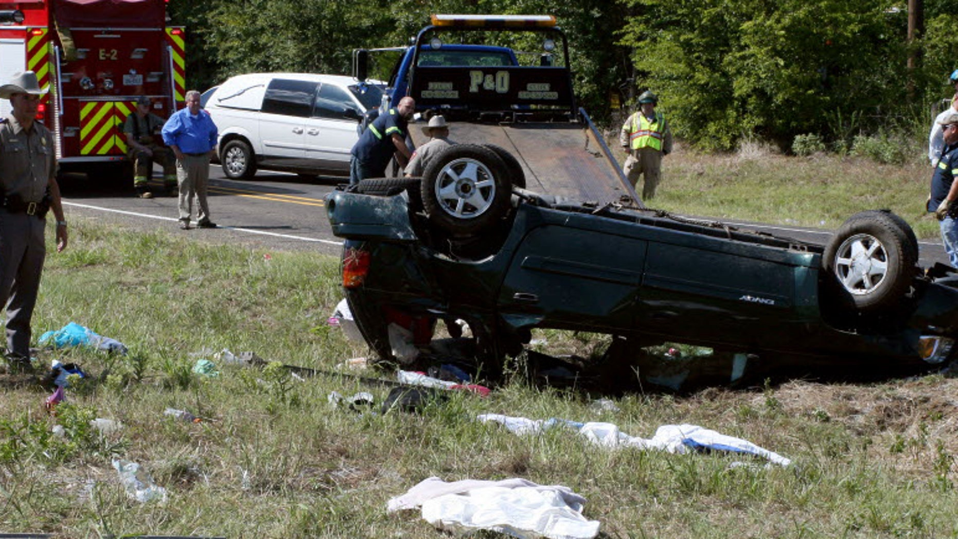 Officials work the scene of an accident in Texas that killed five children. It was caused by an overblown tire. (AP Photo/The Tyler Morning Telegraph, Kenneth Dean)