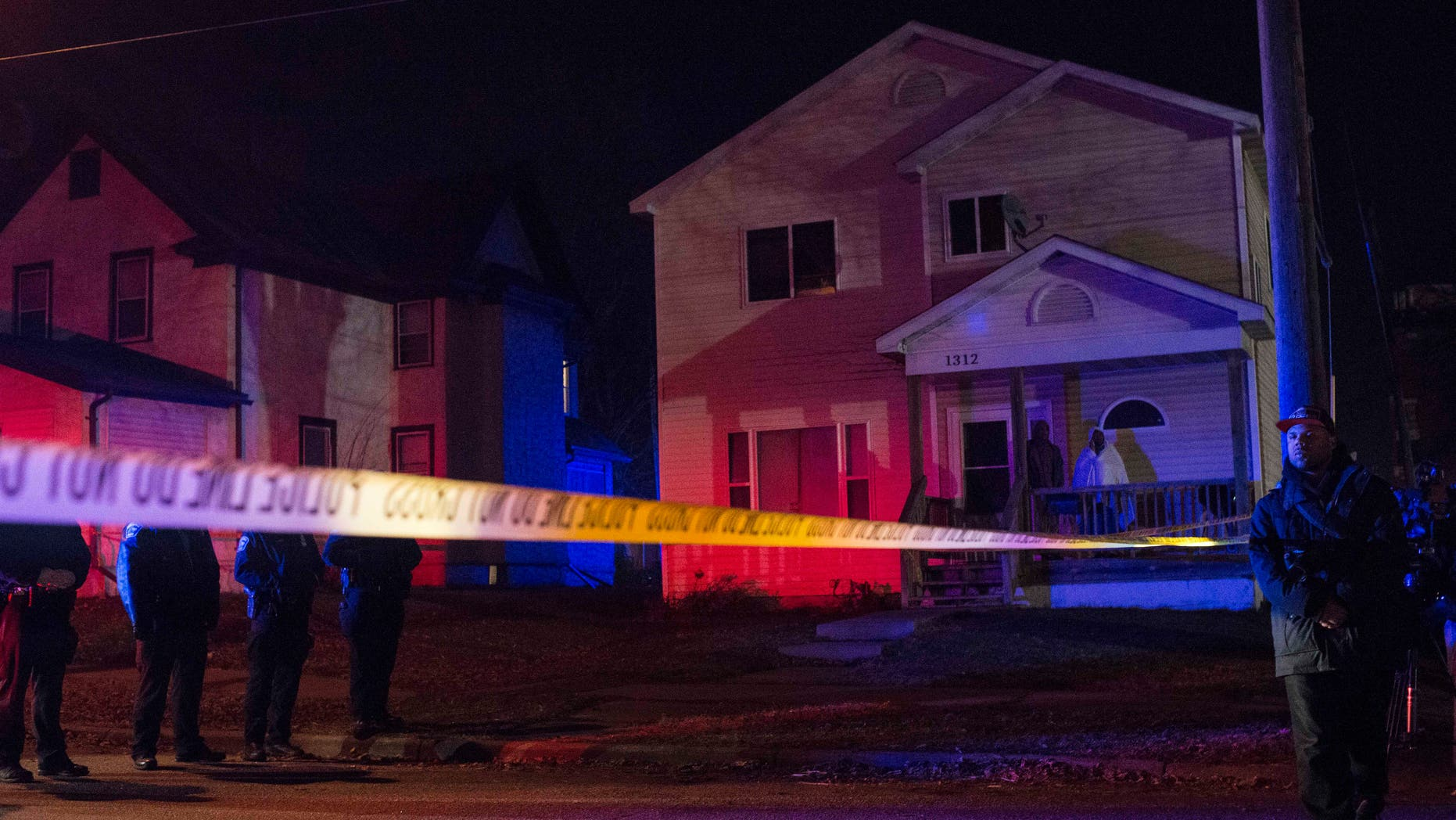 MINNEAPOLIS, MN - NOVEMBER 24: Police line up in front of a crime scene, and two people look on from their porch after 5 people were shot at a Black Lives Matters protest November 24, 2015 in Minneapolis, Minnesota. According to reports, a group of white men allegedly opened fire on the crowd after being escorted away from the encampment. (Photo by Stephen Maturen/Getty Images)
