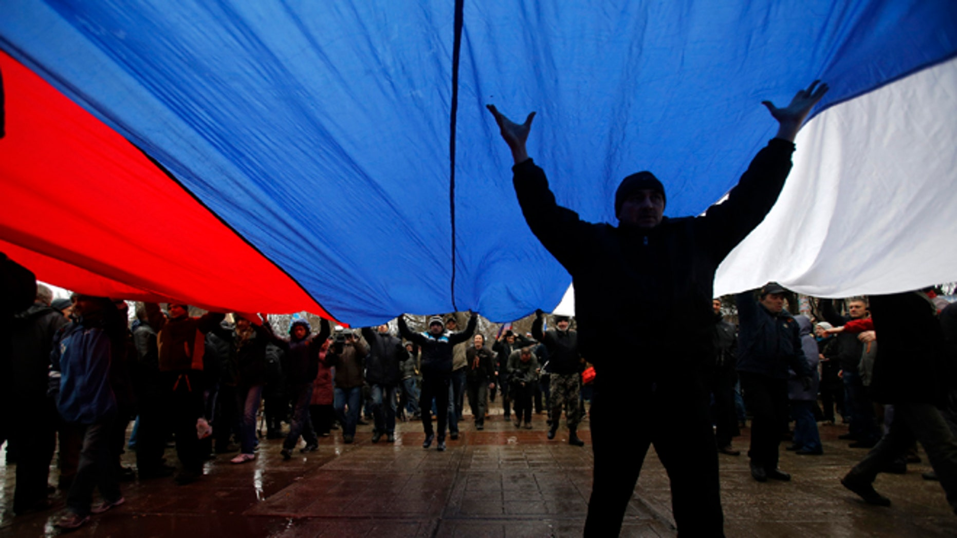 Feb. 27, 2014: Pro-Russian demonstrators march with a huge Russian flag during a protest in front of a local government building in Simferopol, Crimea, Ukraine.
