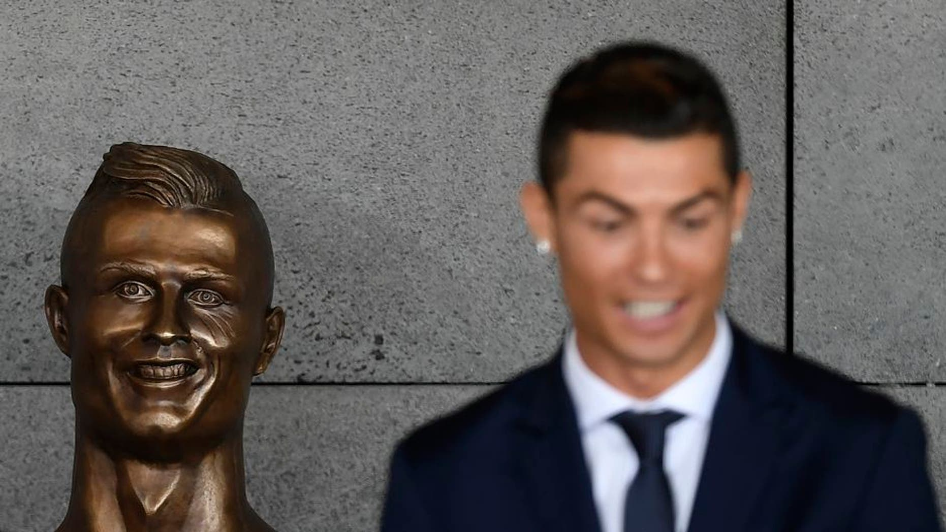 """Portuguese footballer Cristiano Ronaldo stands beside a bust presented during a ceremony to rename Madeira's airport in Funchal as """"Cristiano Ronaldo"""", on Madeira island, on March 29, 2017. Airport of Madeira, the birthplace of Portuguese footballer Cristiano Ronaldo, was renamed today in honor of the quadruple Ballon d'or and captain of the Portuguese team sacred European champion last summer. / AFP PHOTO / FRANCISCO LEONG (Photo credit should read FRANCISCO LEONG/AFP/Getty Images)"""