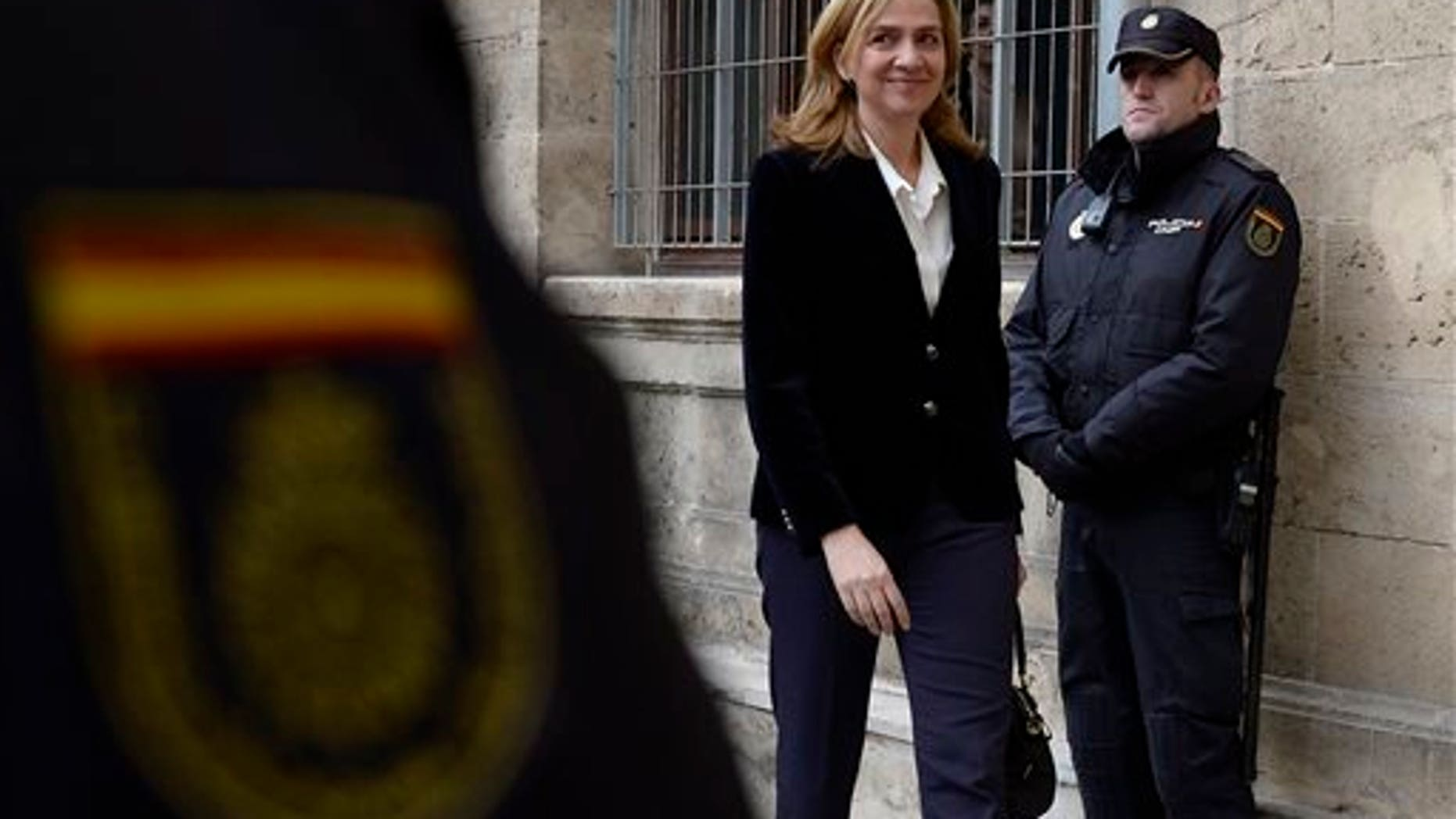 In this Feb. 8, 2014 file photo, Spain's Princess Cristina arrives at the courthouse in Palma de Mallorca, Spain after being named as a fraud and money laundering suspect. A Spanish judge on Wednesday June 25, 2014, has moved closer to indicting Princess Cristina, sister of newly proclaimed King Felipe, in a tax fraud and money laundering investigation centering on her husband. Wrapping up a four-year pre-trial investigation, Palma de Mallorca investigative magistrate Jose Castro kept Cristina on the list of suspects he thinks should stand trial, in her case for money laundering and tax fraud cooperation.