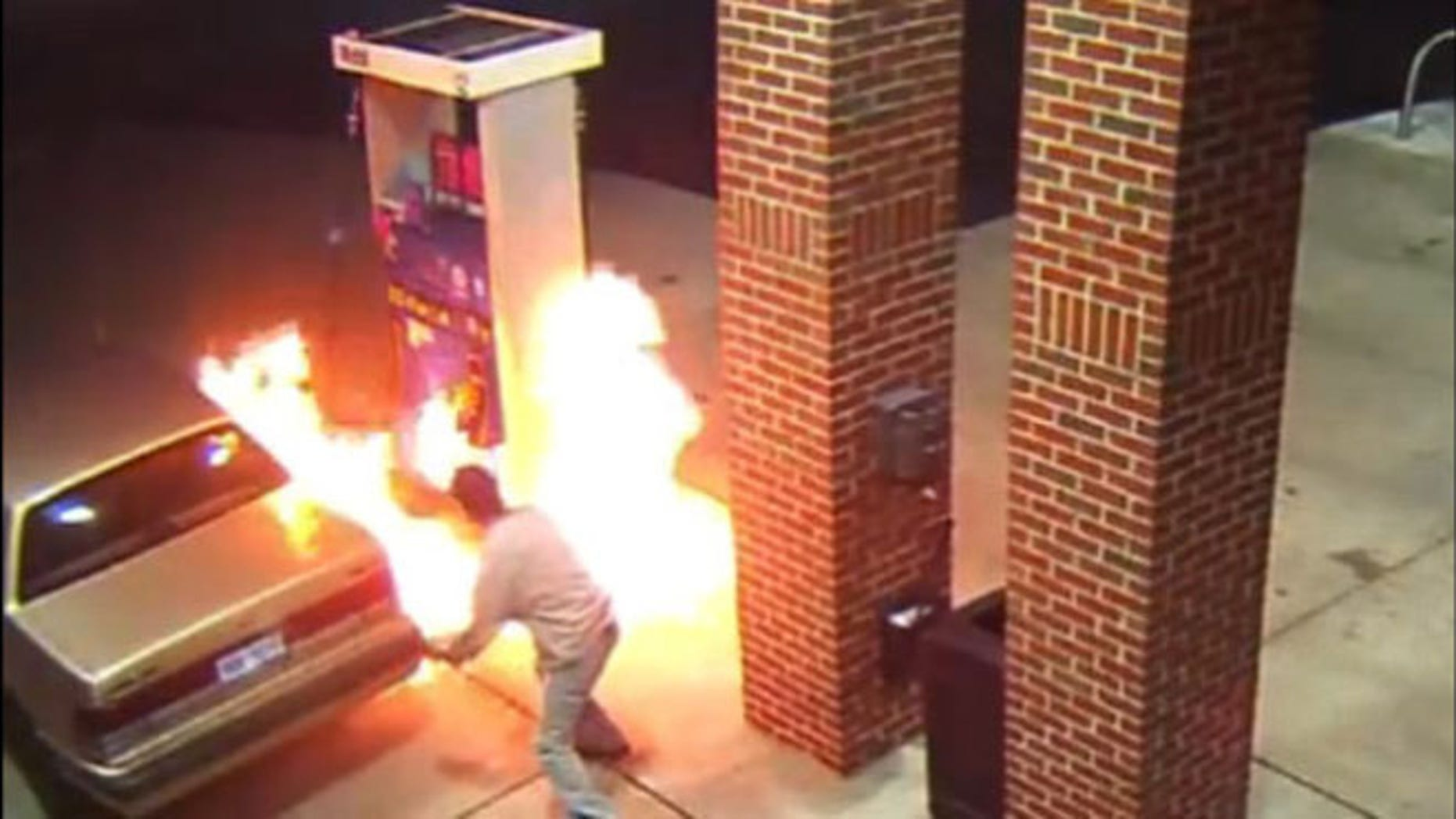 Image from surveillance video shows motorist starting gas station blaze trying to kill spider with lighter.